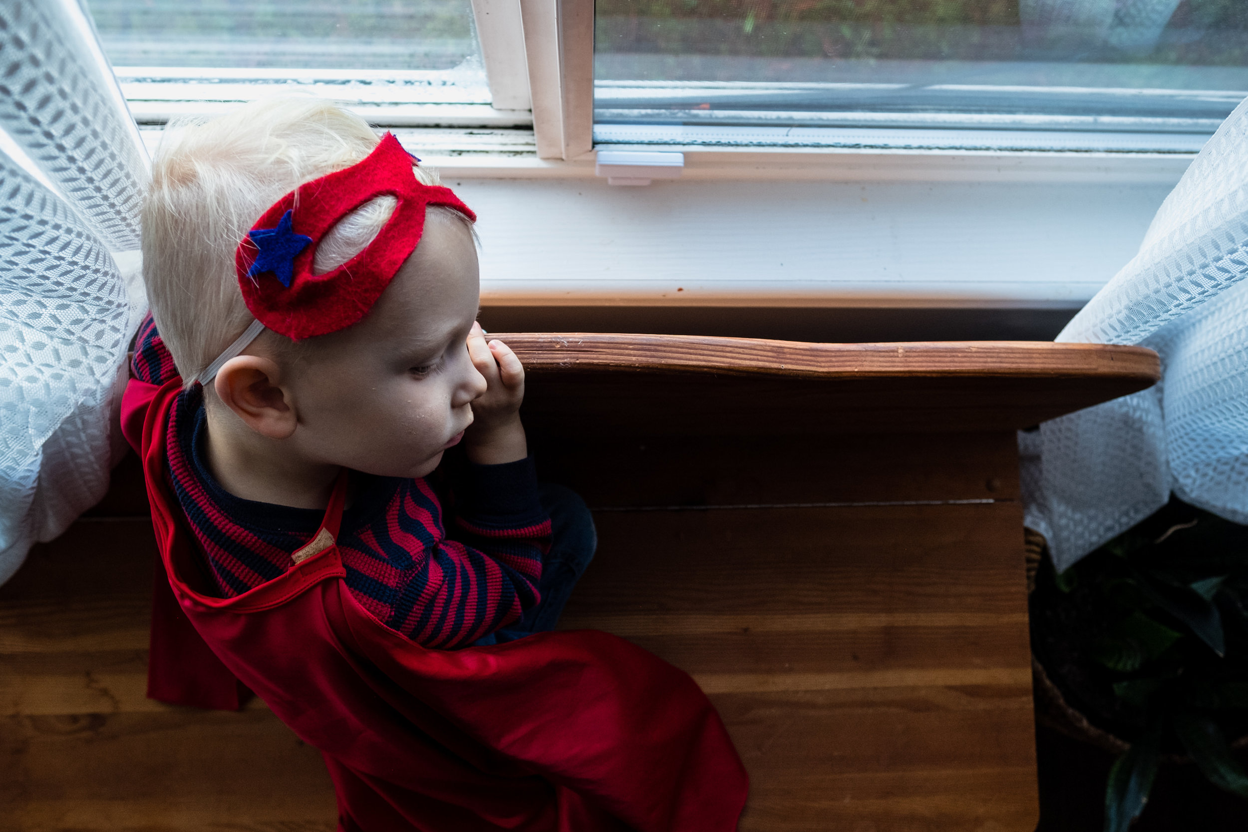 little boy in superhero costume gazing out of window in vancouver canada
