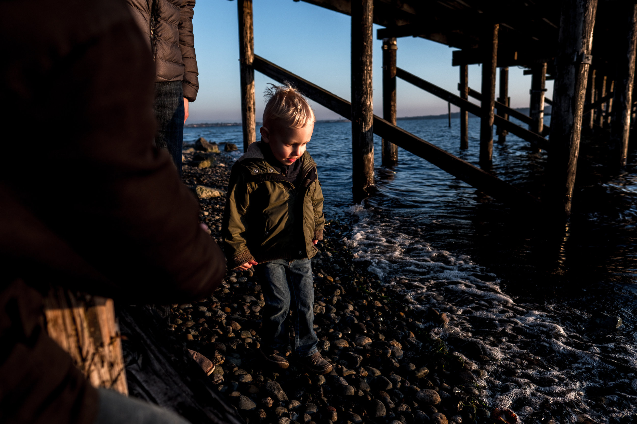 little boy toddler walking under dock at ocean
