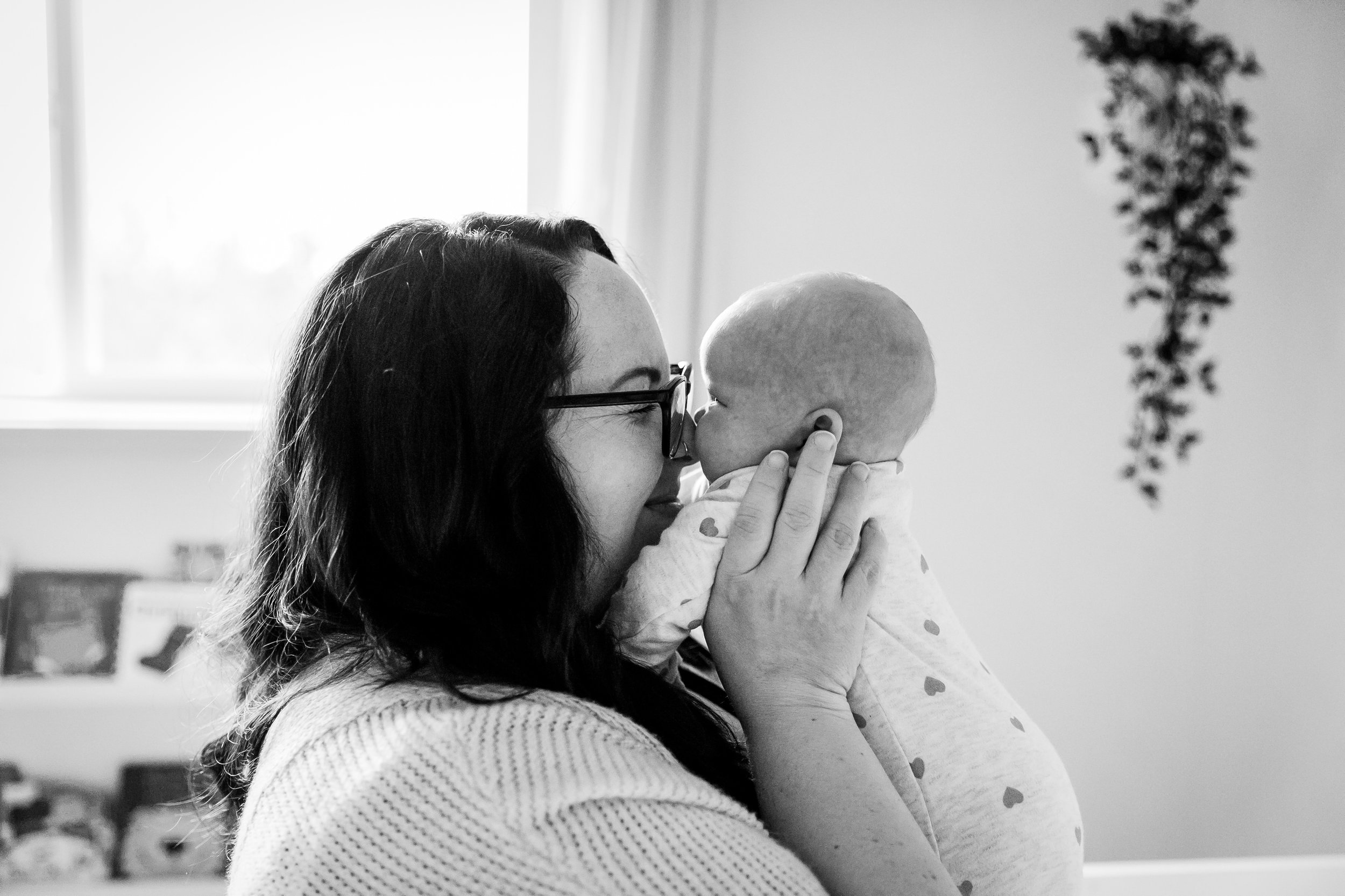 mom kissing baby in nursery laughing vancouver newborn photography