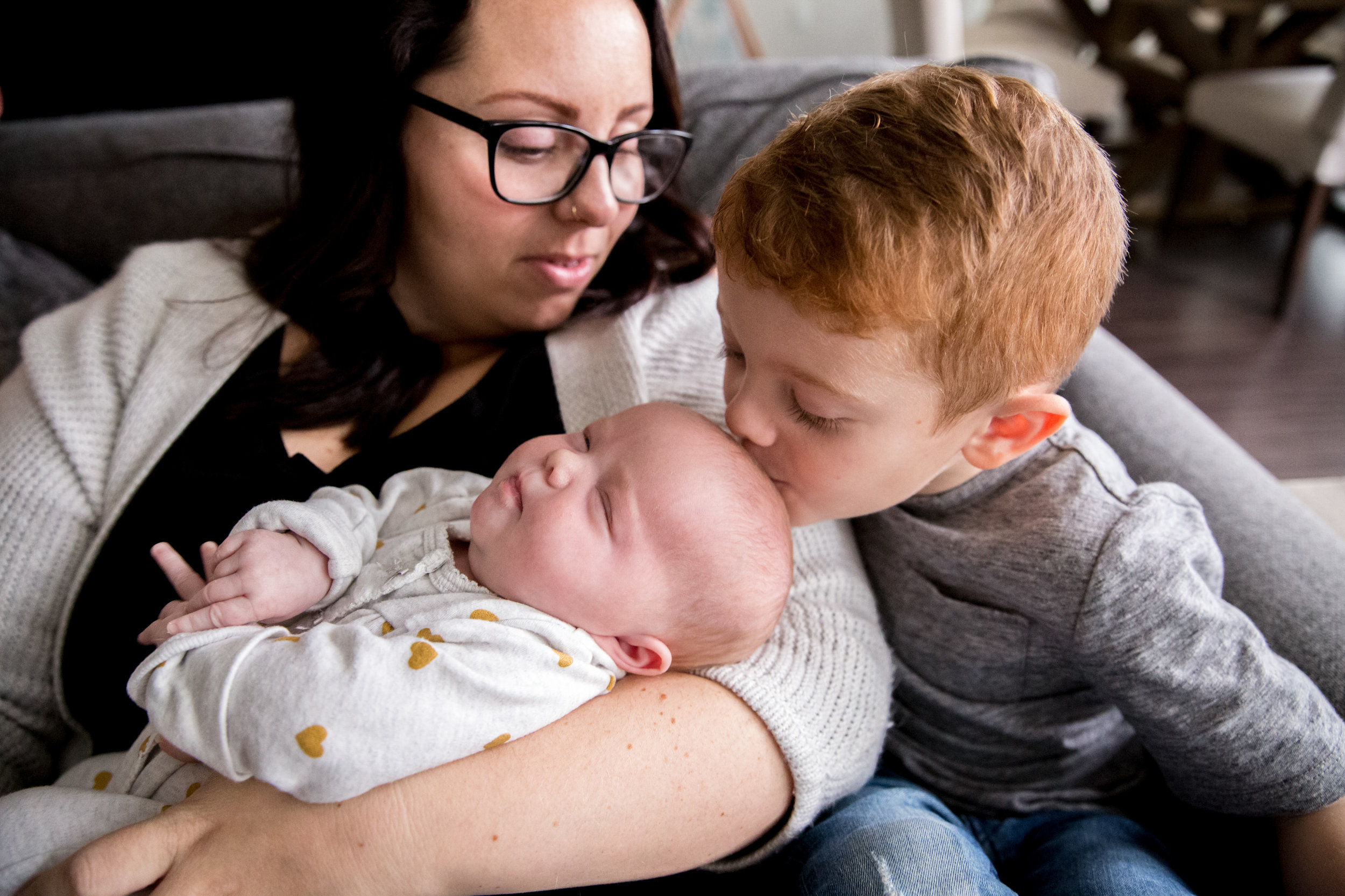 brother kissing baby sister with mom holding baby in vancouver canada