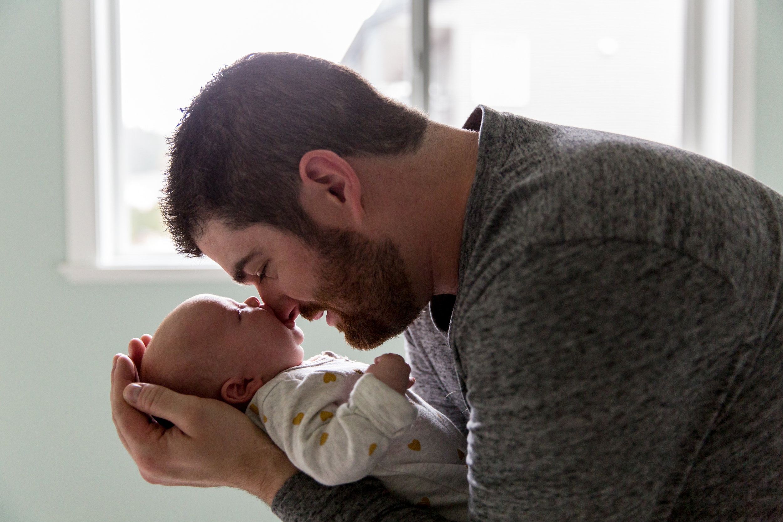 dad and baby on bed by window vancouver