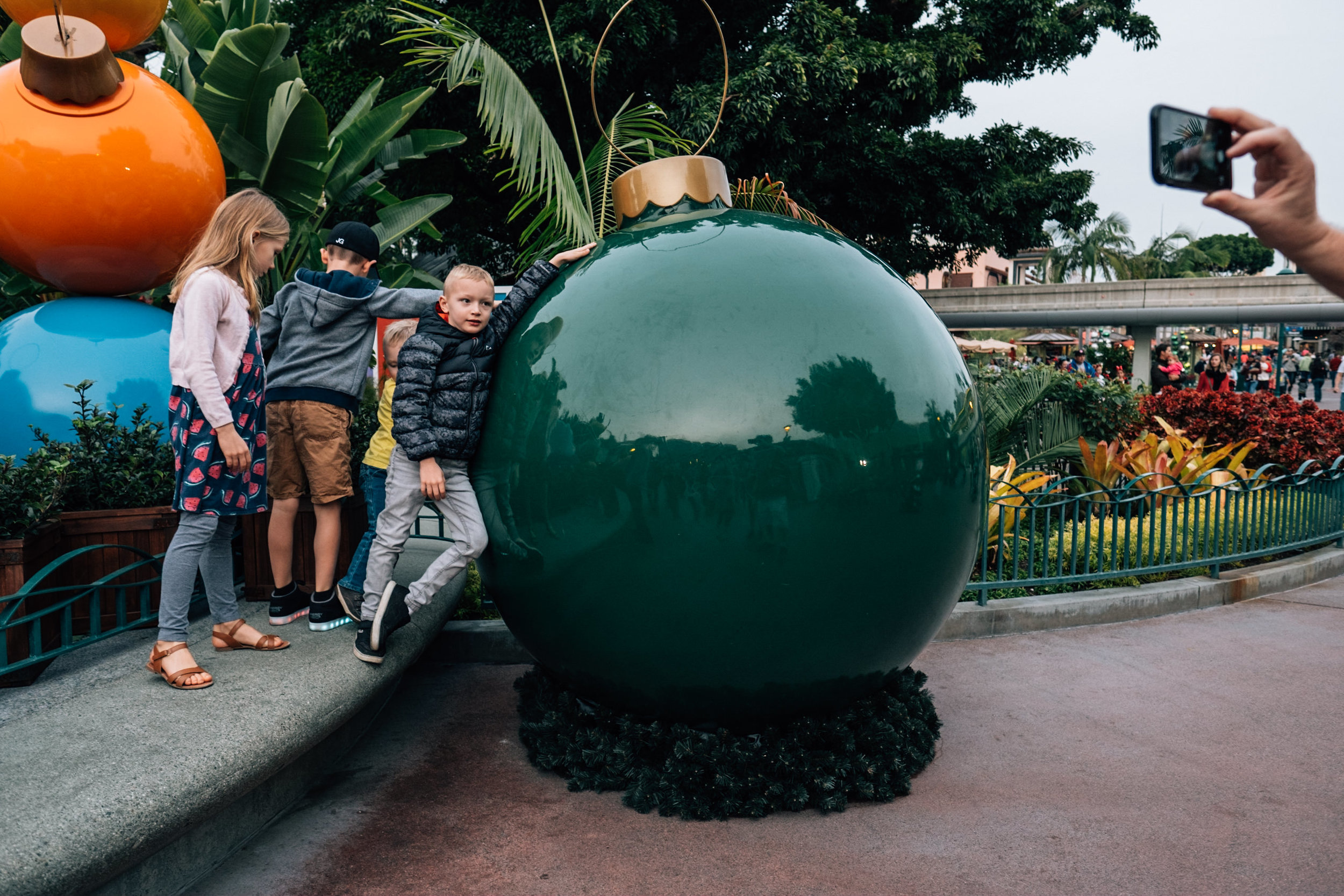 kids with giant christmas bulb at downtown disney