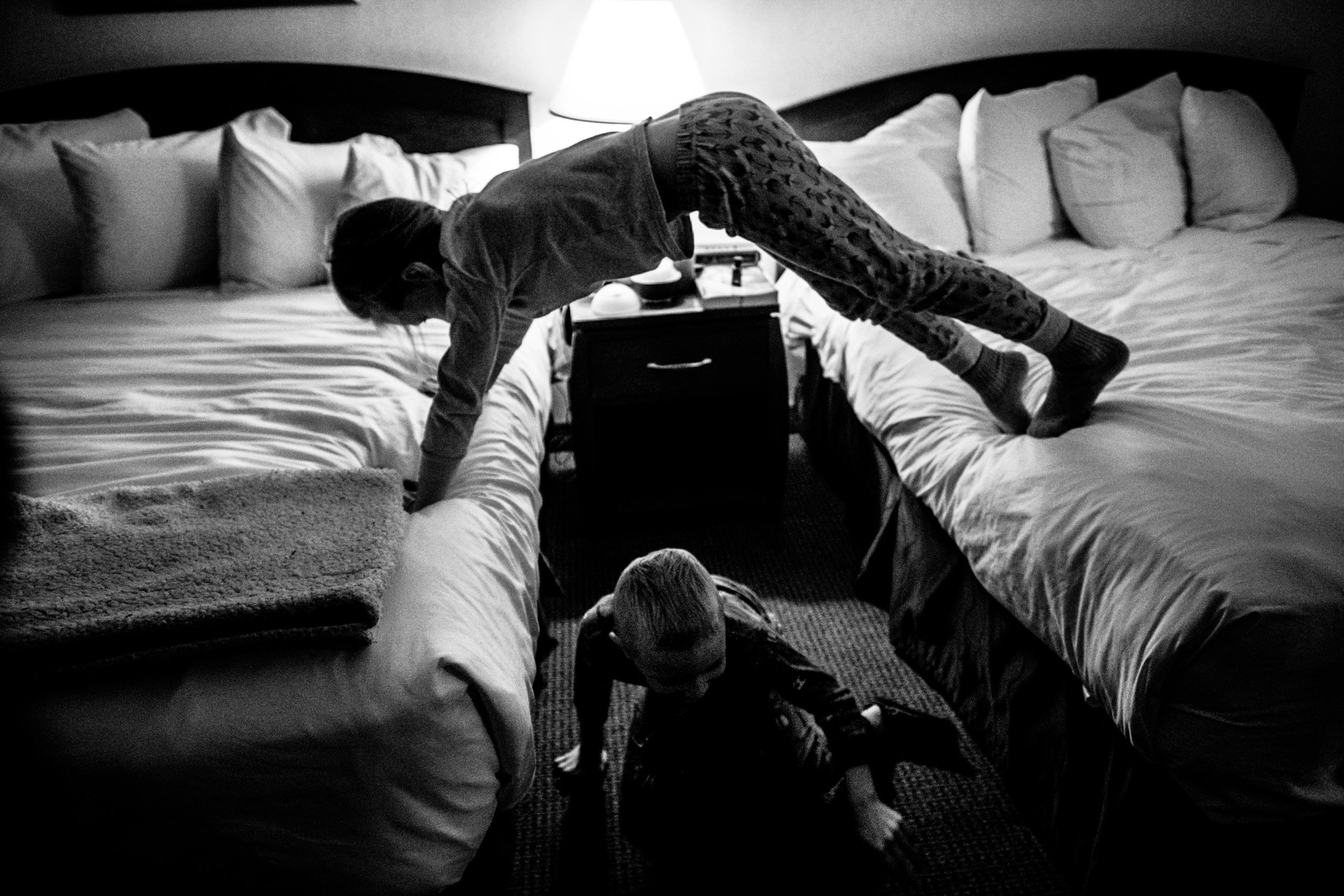 kids in hotel room playing on beds making a bridge with one child crawling under