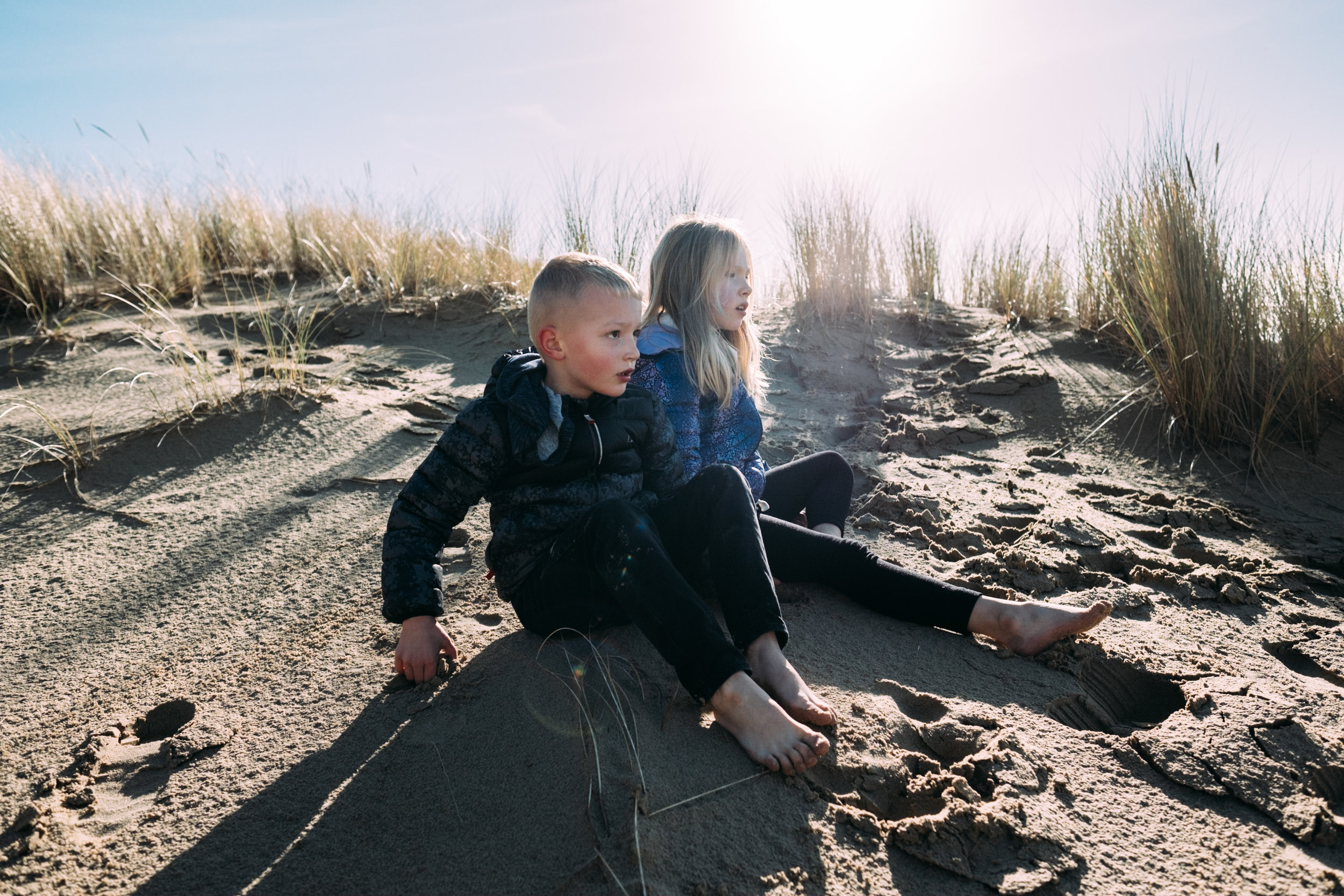 children sitting on sand dunes in oregon