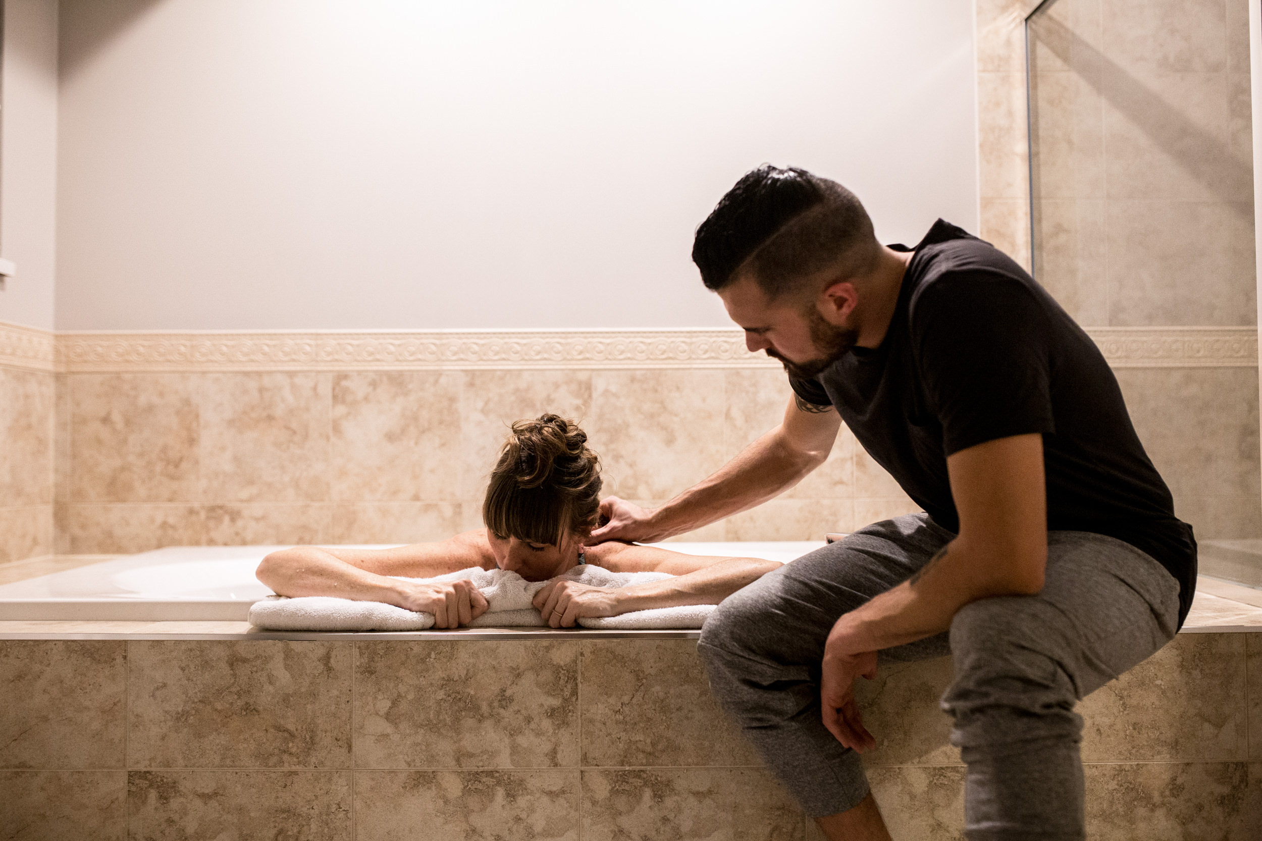 dad supporting mom in the bath tub with his hand on shoulder
