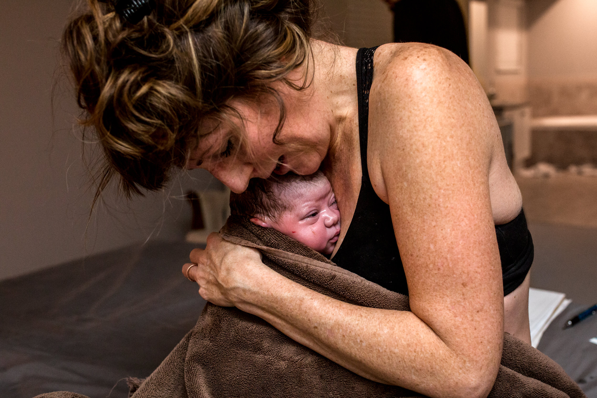 mom holding her newborn baby after delivery