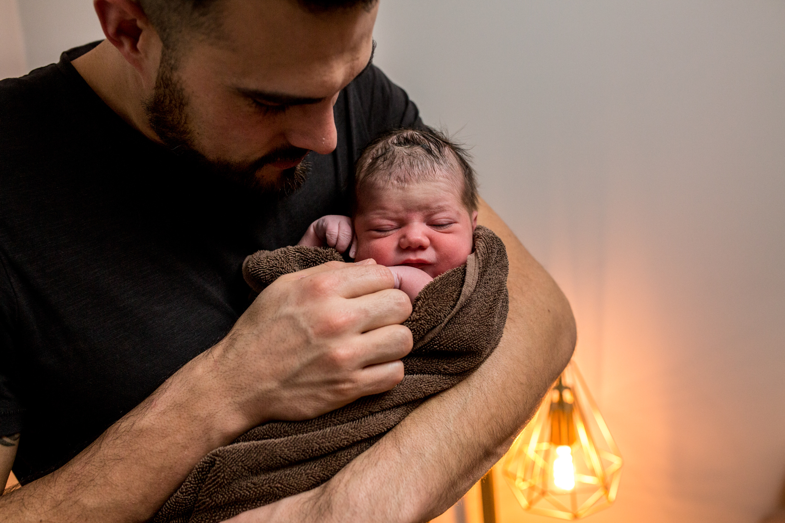 dad standing holding baby in a brown towel