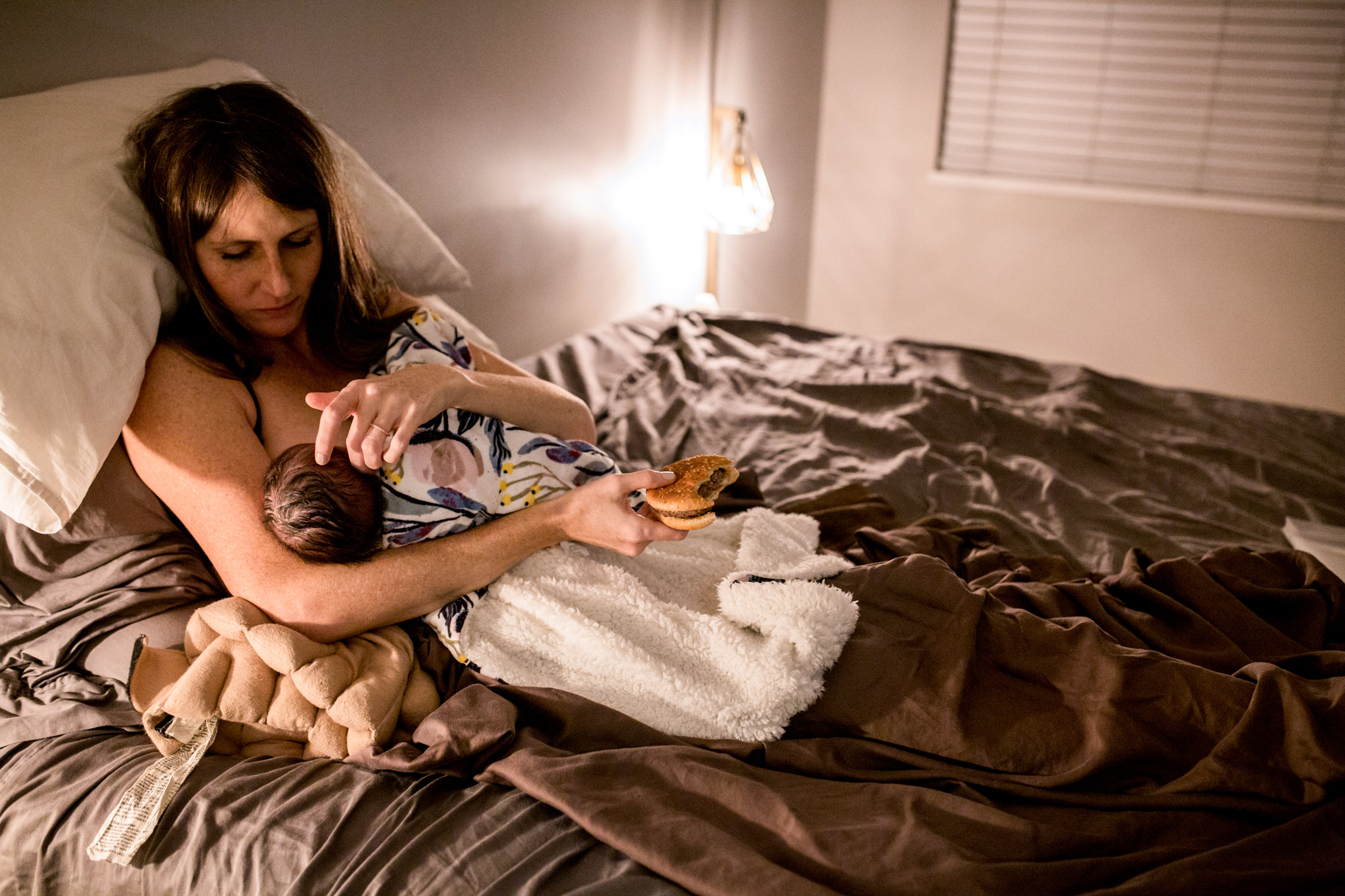 mom eating burger after home birth while nursing