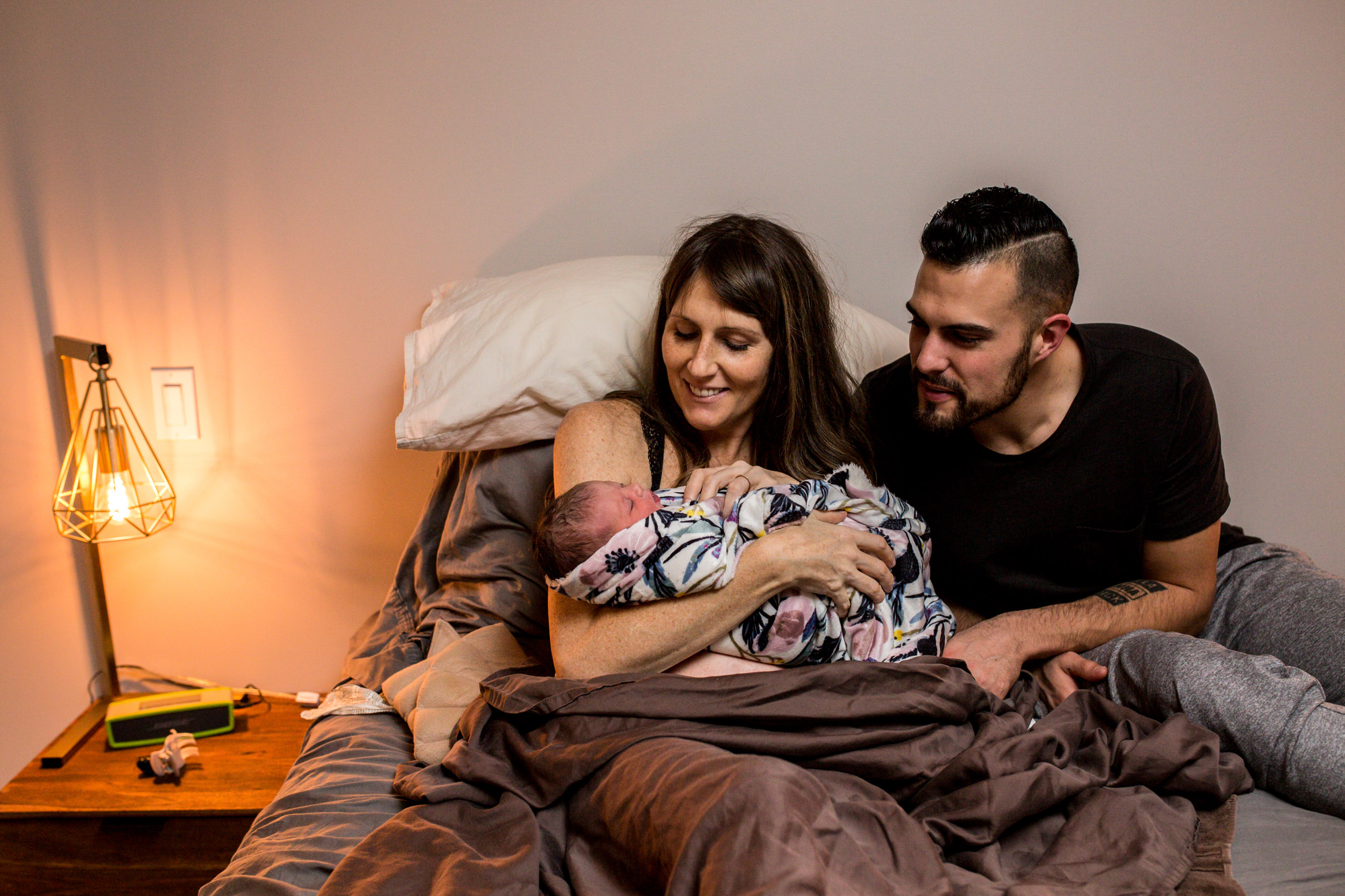 parents with newborn on bed