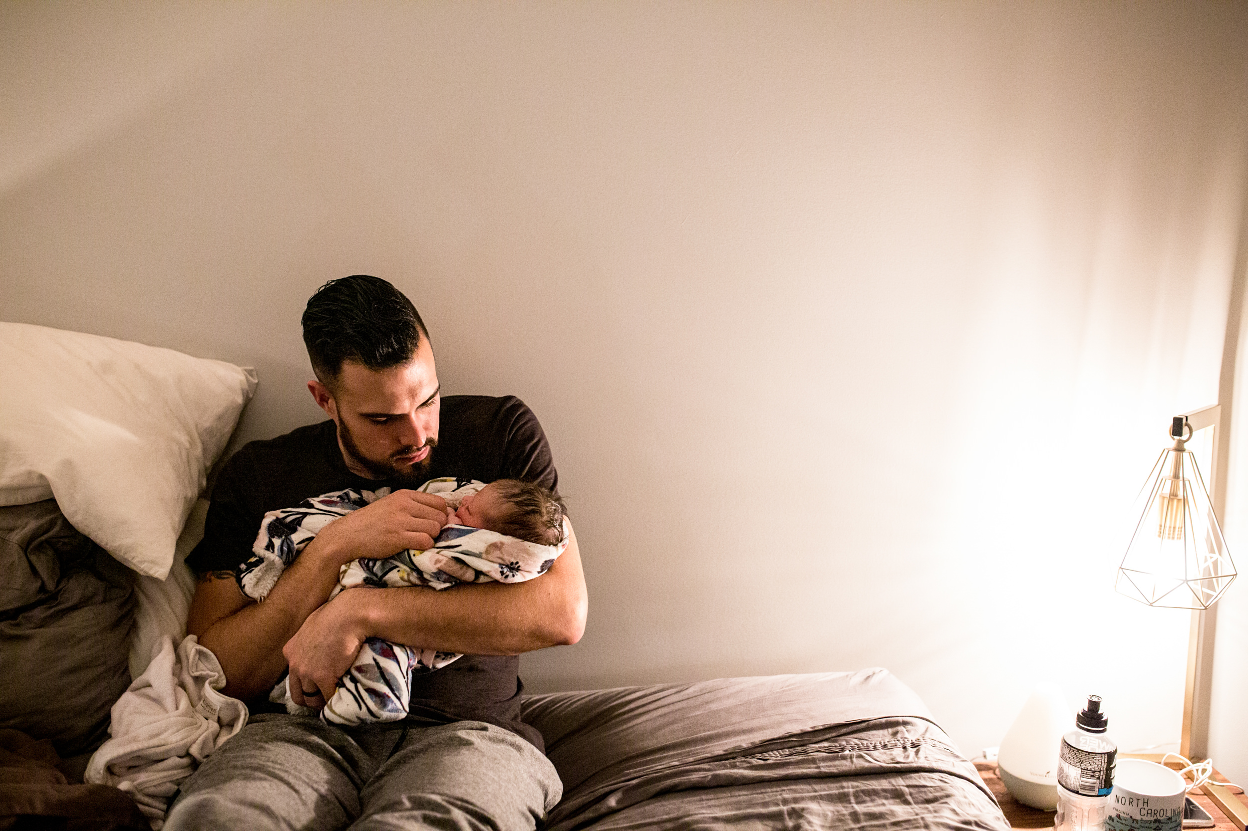 father holding his new baby on bed after home birth