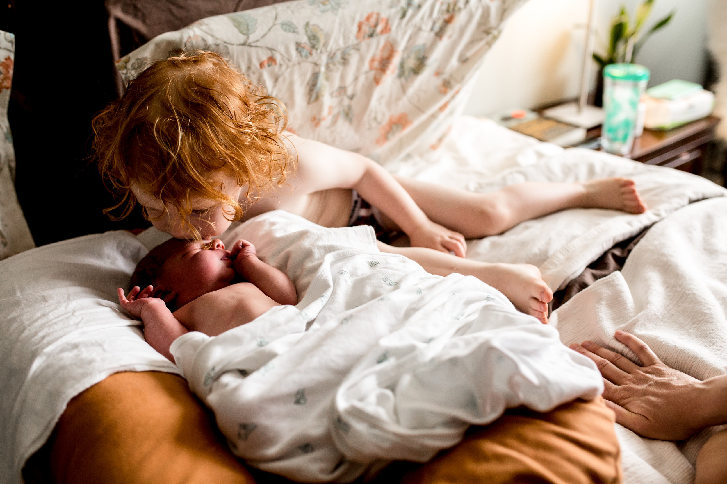 little boy kissing his newborn baby brother