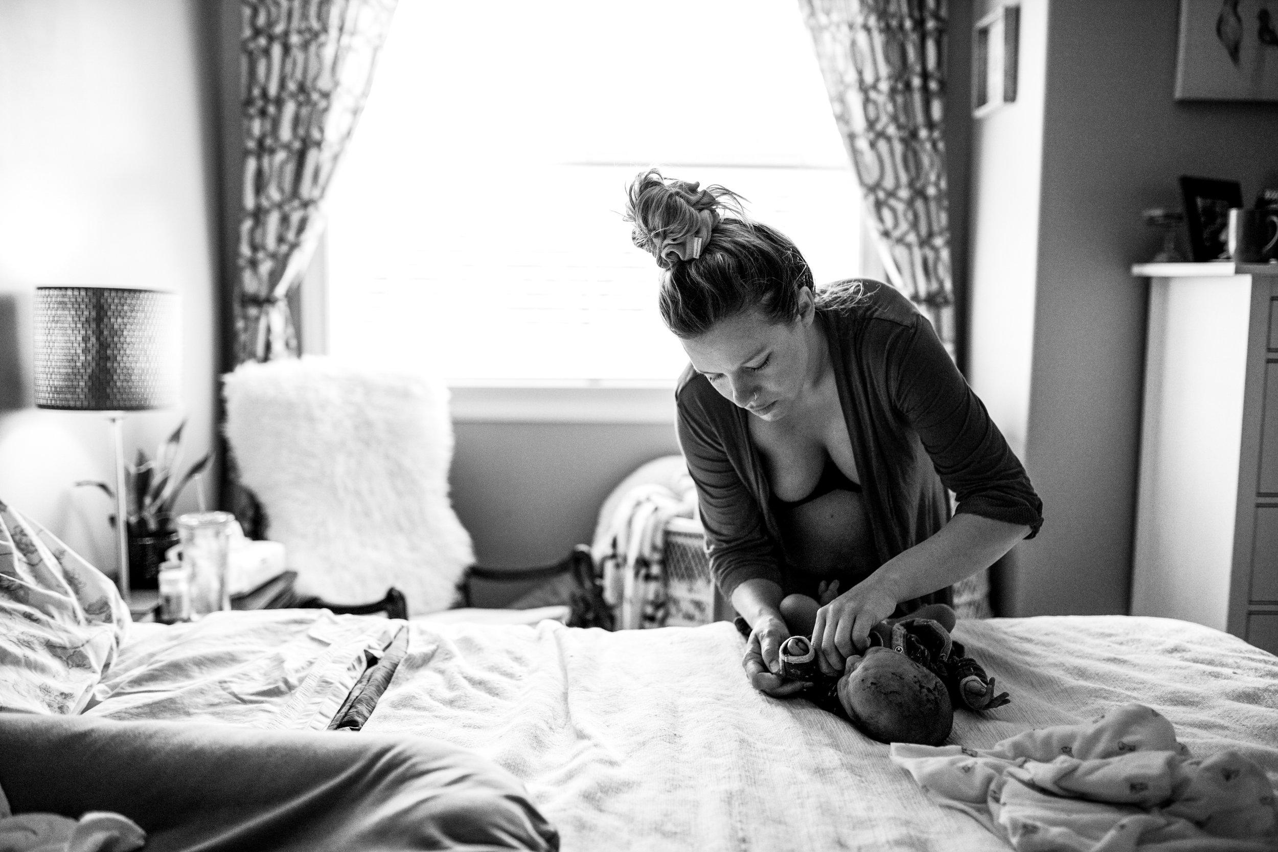 woman-dressing-her-newborn-on-bed.jpg