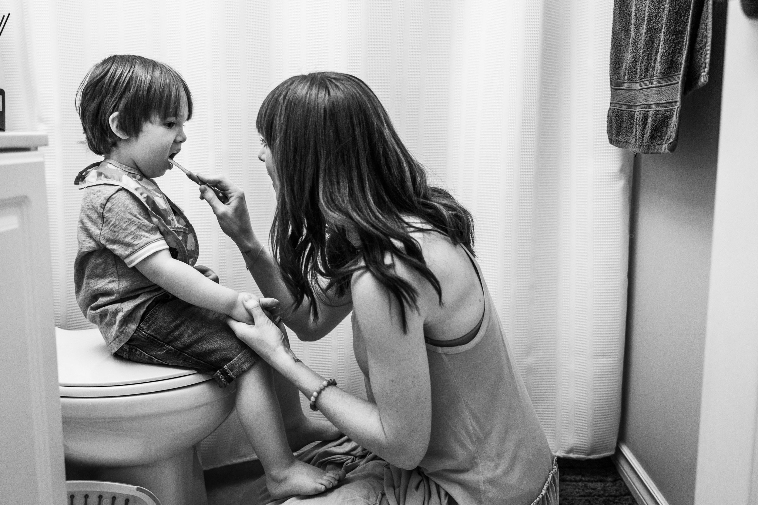 mom brushing young toddler's teeth on toilet in bathroom