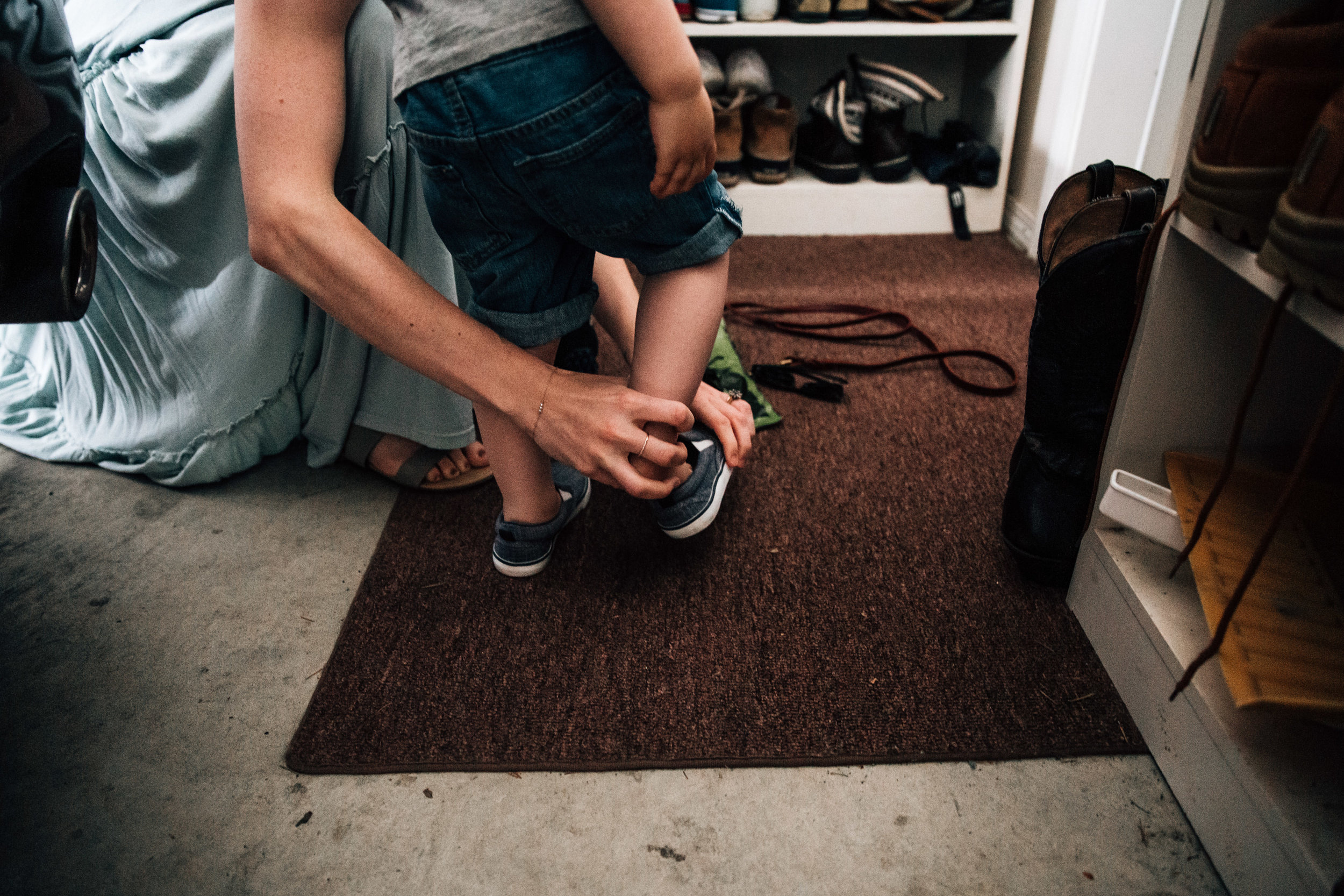 mom putting shoes on toddler boy in garage
