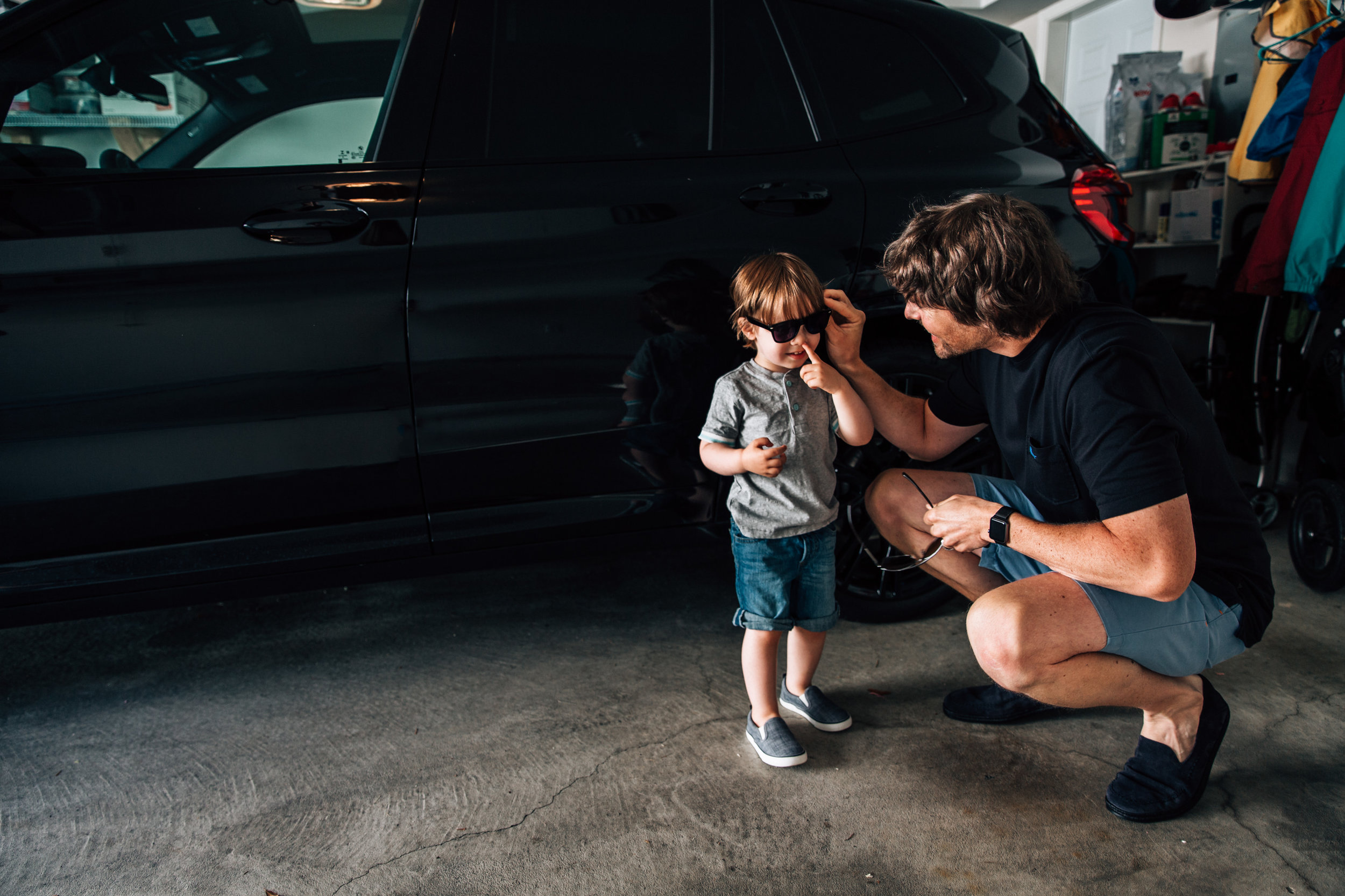 dad squatting down and putting glasses on young child in the garage