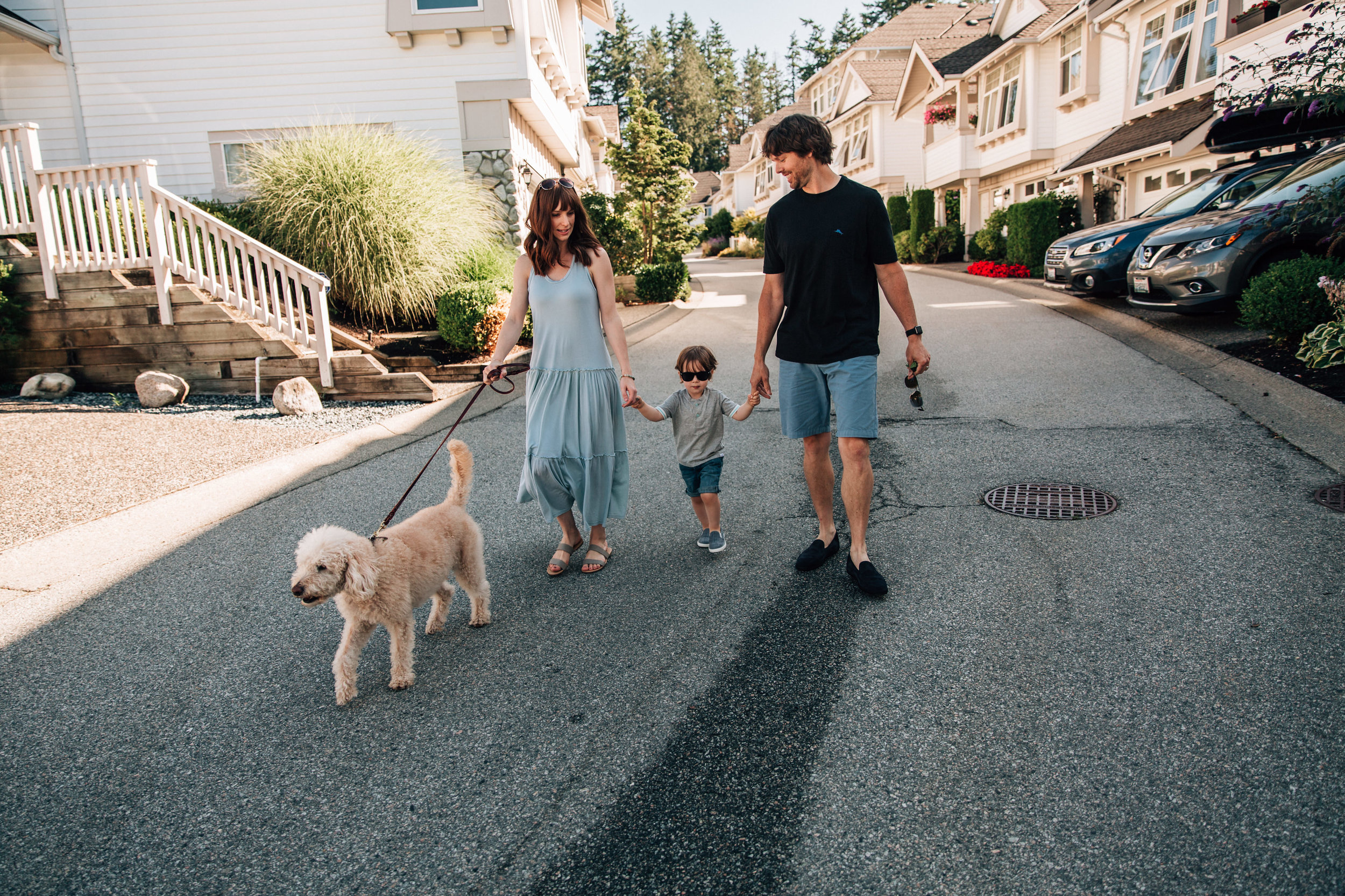 family of three walking down the road with their dog