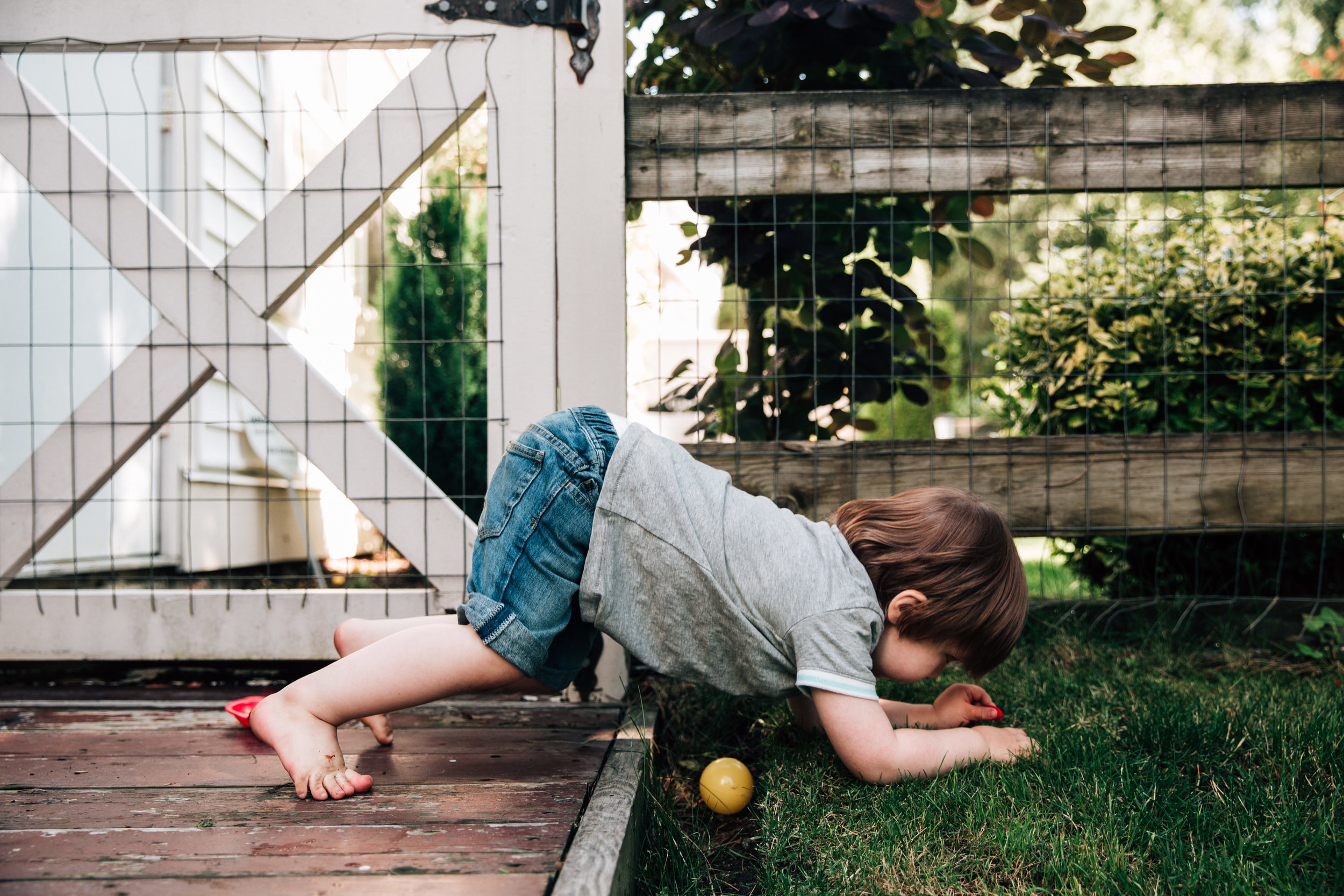 toddler on all fours climbing over a small ditch with a ball in it