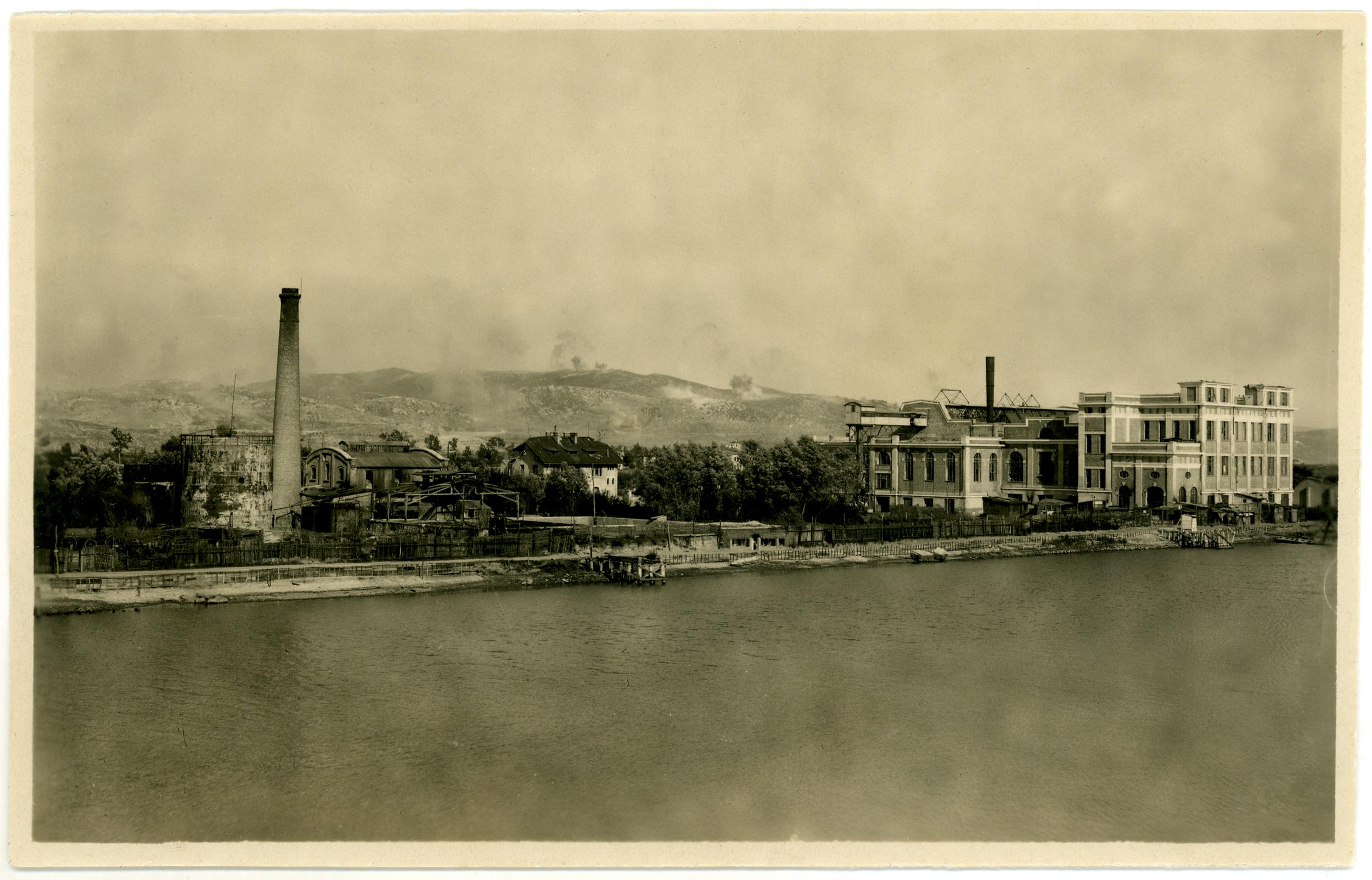 Sopra: vista degli stabilimenti dell'Adriawerke con sullo sfondo le quote contese 85 e 77 sotto bombardamento italiano