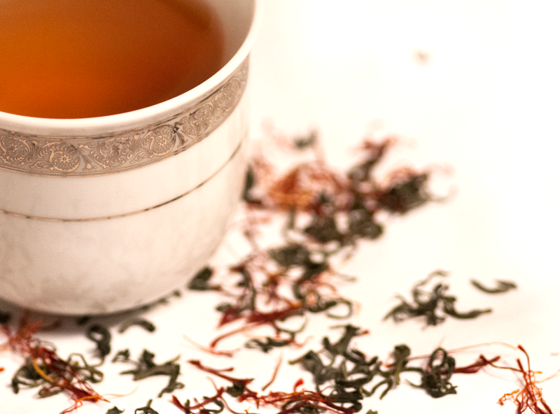 Teacup on saffron threads and green tea leaves
