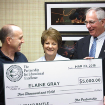 Flanked by her husband Kevin Gray (left) and Partnership President John Fassero, Jr., Elaine Gray receives her check for $5,000.