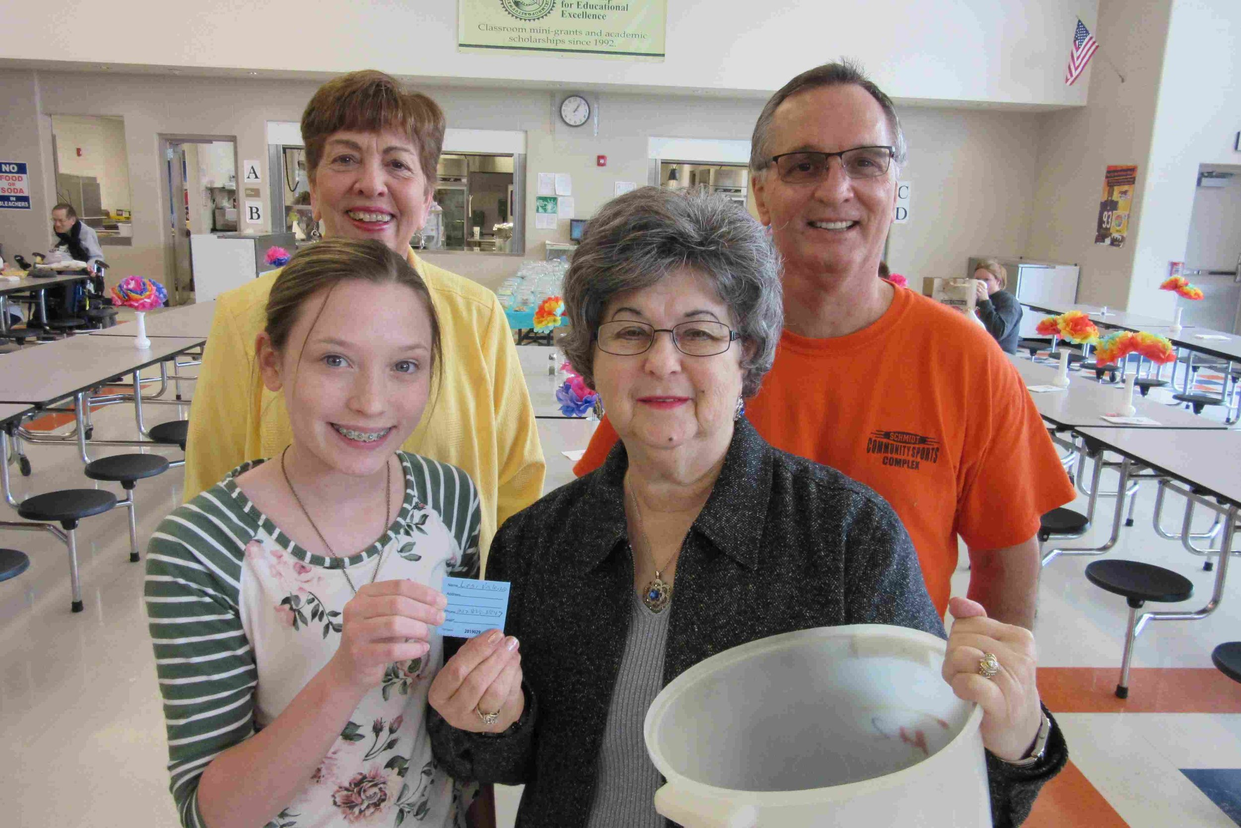 Shelbee Geisler and Rose Tebbe hold Lori Valerio's winning ticket. Carole Scheller and Don Throne, both Partnership directors look on.