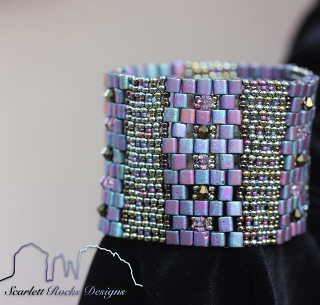 *⚜️Violet Galactic Cuff Bracelet ⚜️* ________________________________ This stylish cuff is woven with a myriad of metallic silver, blue, and violet shades.  Glass beads in round and cube shapes tile together perfectly to showcase glimmering rows of light amethyst shade and dorado bronze Swarovski crystals 💎and elevate this design into a glamorous yet edgy statement piece.  Silky smooth upon the wrist, it is effortlessly donned with two concealed metal snaps that create the perfect seamless enclosure.