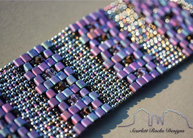 "At my trunk shows, the Galactic Cuff has garnered lots of attention because of its lovely texture.  People adore the cool feeling of sumptuous beaded ""fabric"" against the skin.  It has a fluidity to it that is so satisfying.  It has also become a fave as there is no visible clasp (a concealed double snap closure) which means the beadwork pattern wraps completely around the wrist."