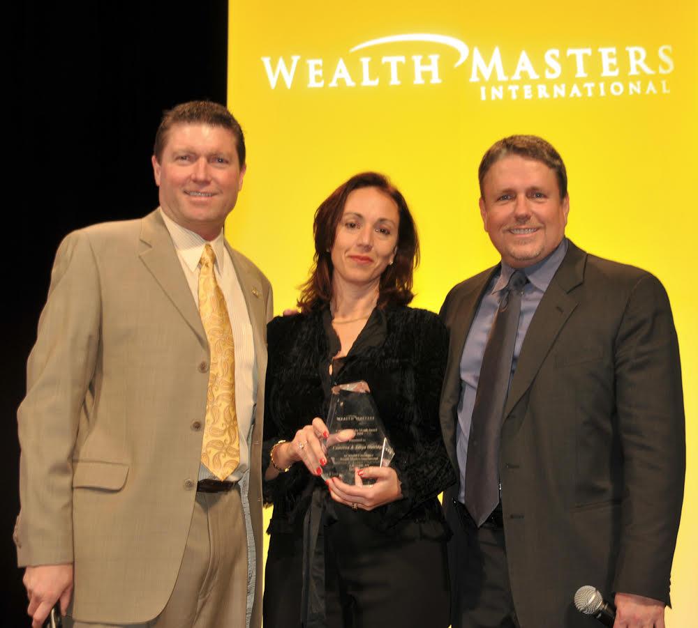 Tanya receiving a Sales & Leadership award from Wealth Masters International Founders, Karl Bessey & Kip Herriage