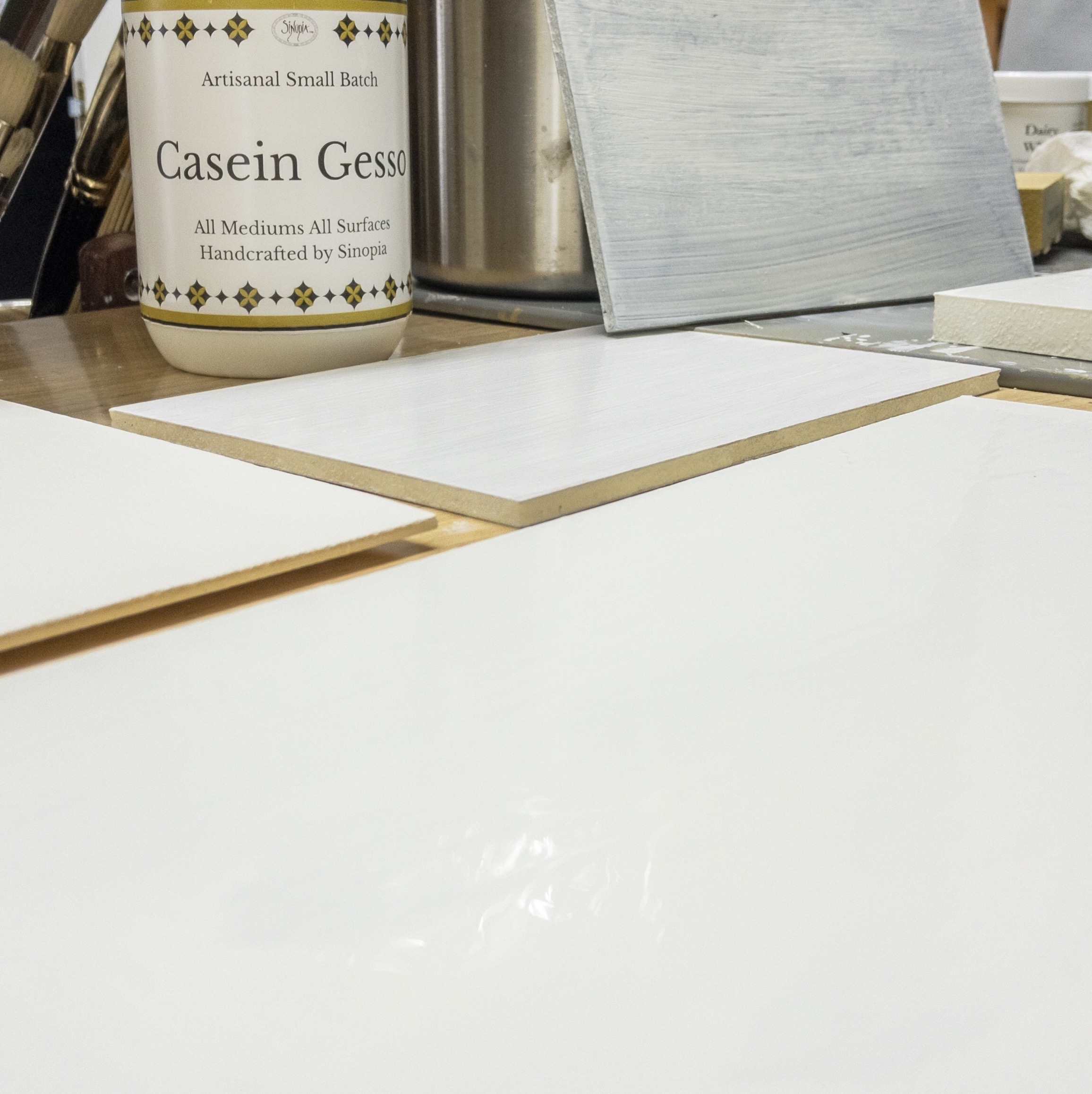 Casein gesso applied to different substrates. The black foam core panel (top right) demonstrates this casein gesso's translucency. At least two coats will be required for a full coverage.