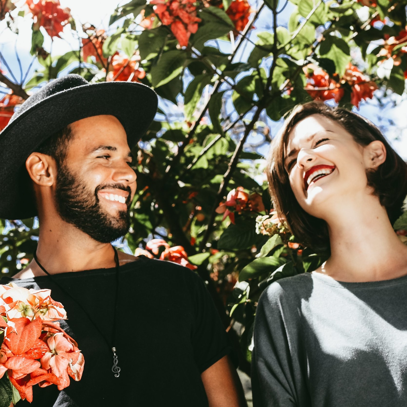 couple-laughing-outdoors-under-flowered-vine.jpg