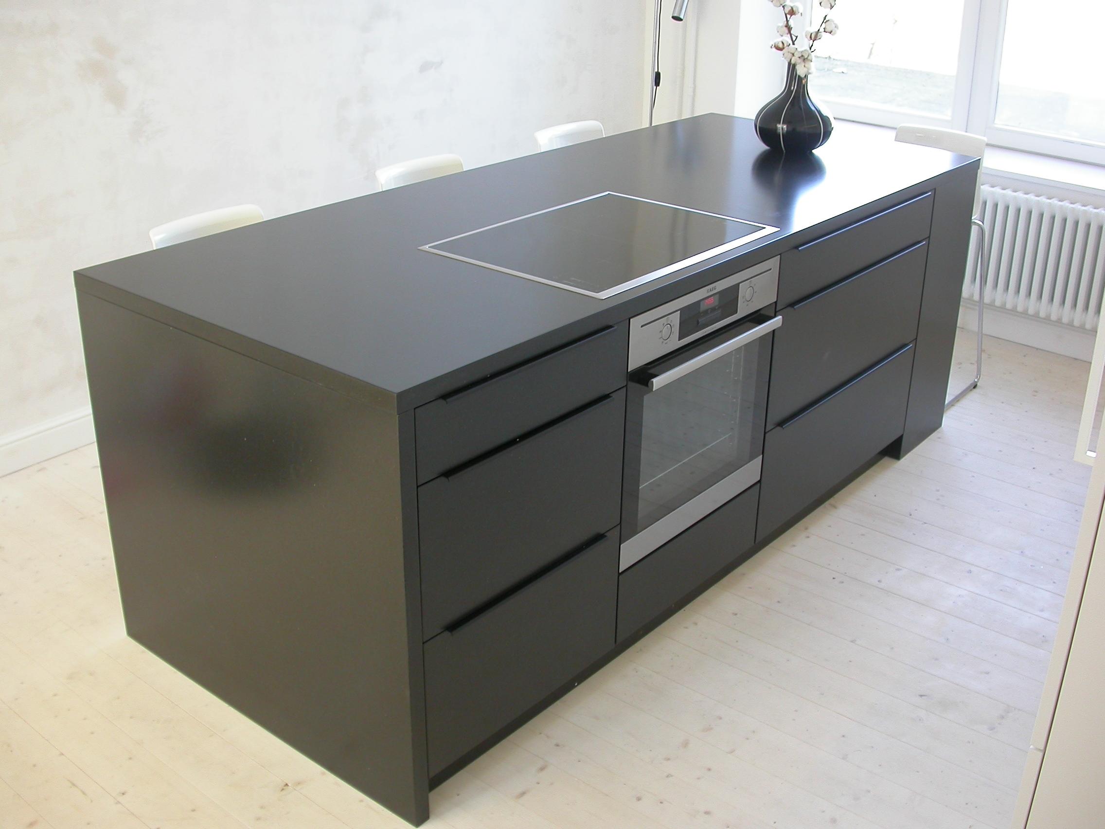 Küchenblock aus schwarzem MDF, Schubladen mit Griffleisten aus Aluminium schwarz matt.