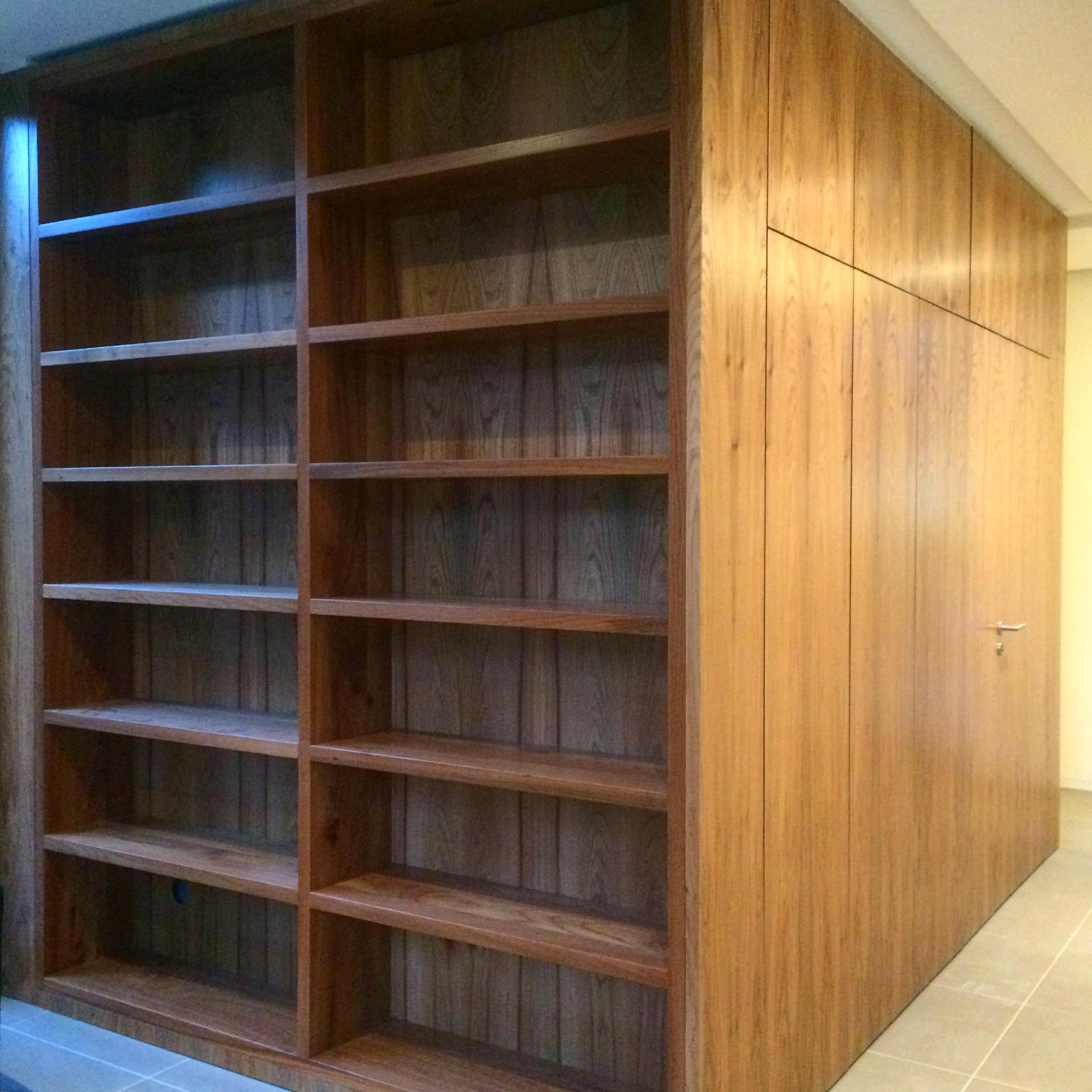 Bücherregal aus Rüster / Ulmenholz mit integrierter Garderobe und WC Tür.