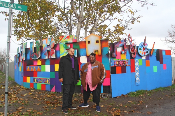 Scape Martinez, left, a visual arts consultant for Youth Action Team, and Isaiah Phillips, Youth Action Team's community arts liaison, stand in front of an art installation announcing the future home of the East Palo Alto Youth Arts and Music Center on Jan. 5, 2016. Photo by Veronica Weber.