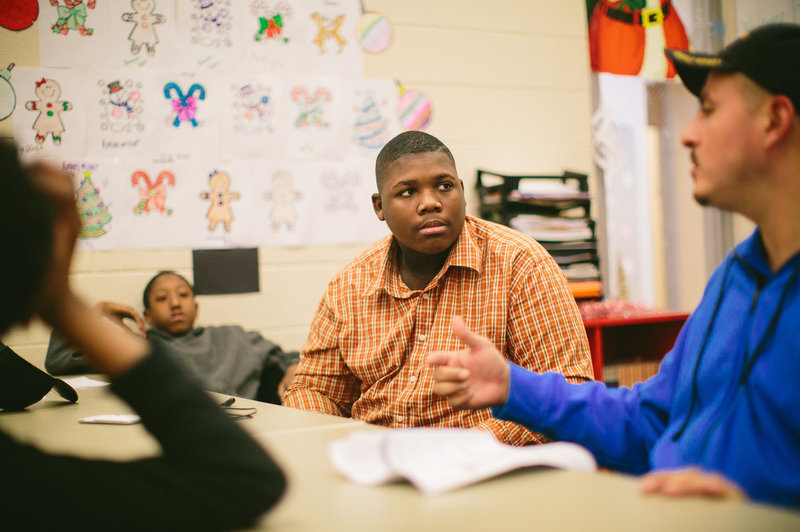 Jim Courtney-Clarks, 15, talks with Army veteran Alberto Bóleros during the Urban Warriors program in December. The Chicago program is designed to bring together veterans and youth who have been exposed to the city's violence.   Alyssa Schukar for NPR