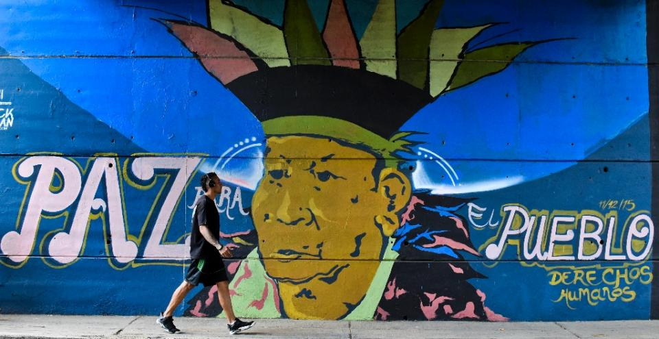 """A man walks past graffiti that reads: """"Peace for the people, human rights"""" in the Chipichape neighbourhood in Cali, Colombia on January 9, 2016 (AFP Photo/Luis Robayo)"""