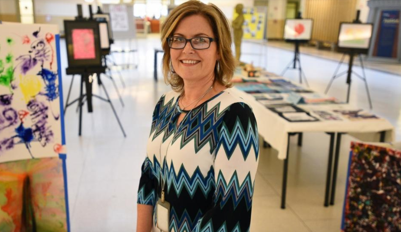 Juvenile Probation Officer Fiona Bycroft-Ryder stands in front of Arts Alternative, an exhibit featuring the work by young people in the juvenile court in the Worcester Trial Court lobby. Photo by Christine Hochkeppel.
