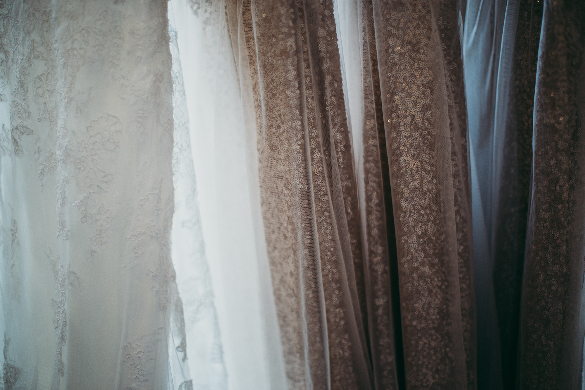 Close up of details of white wedding dress and gold with sequins bridesmaids dresses.
