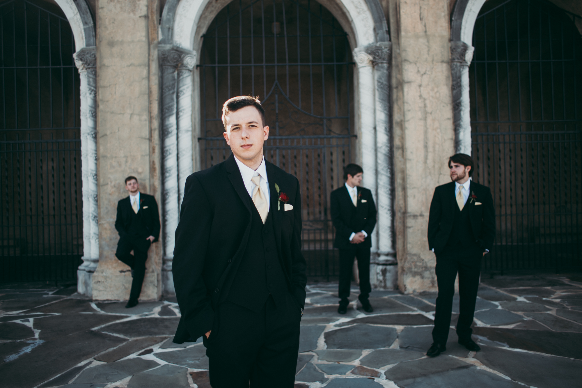 Three groomsmen and a groom standing in the shade wearing suits.