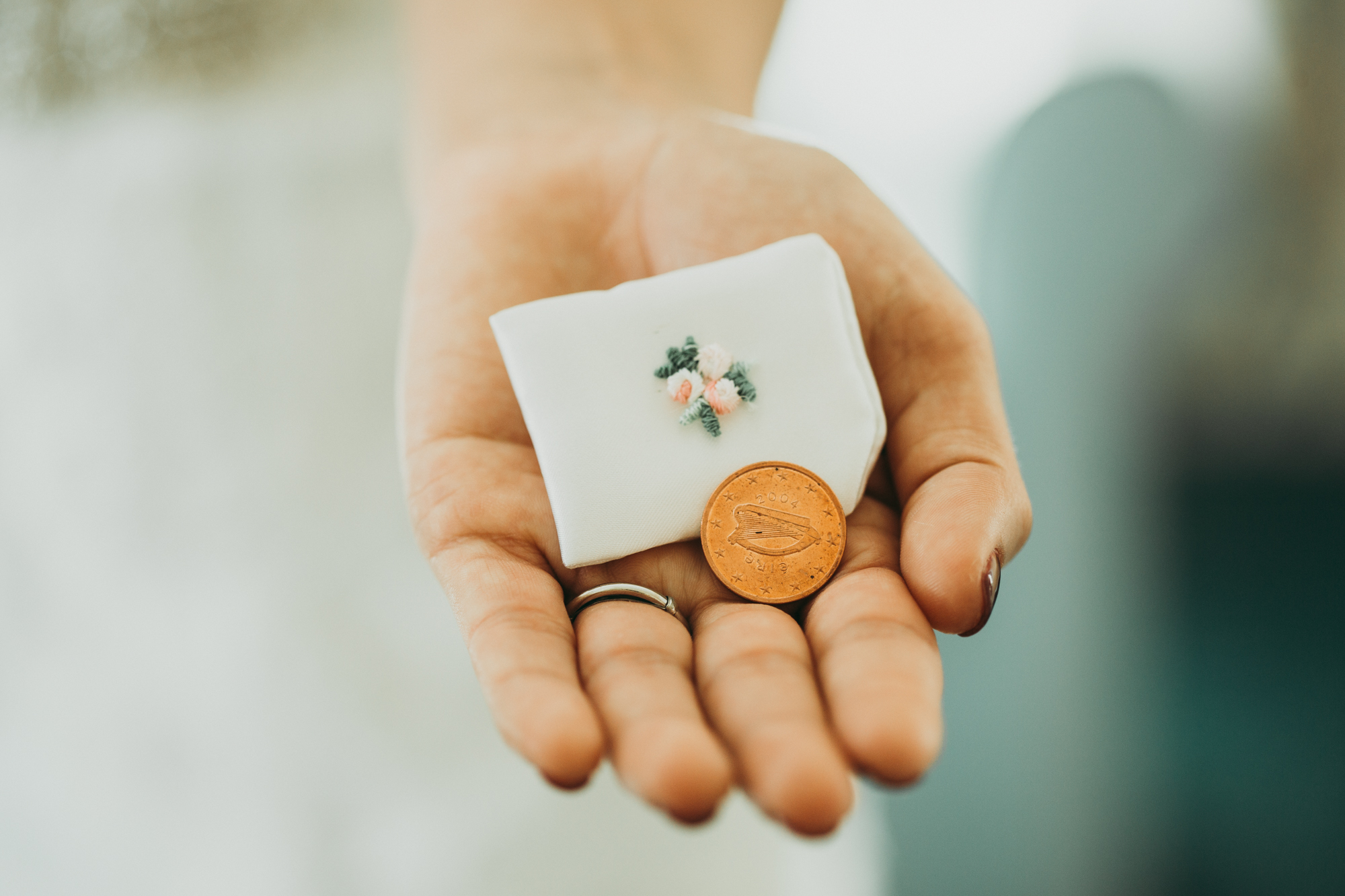 Hand with a ring holding a penny and a pouch with a flower embroidered detail.