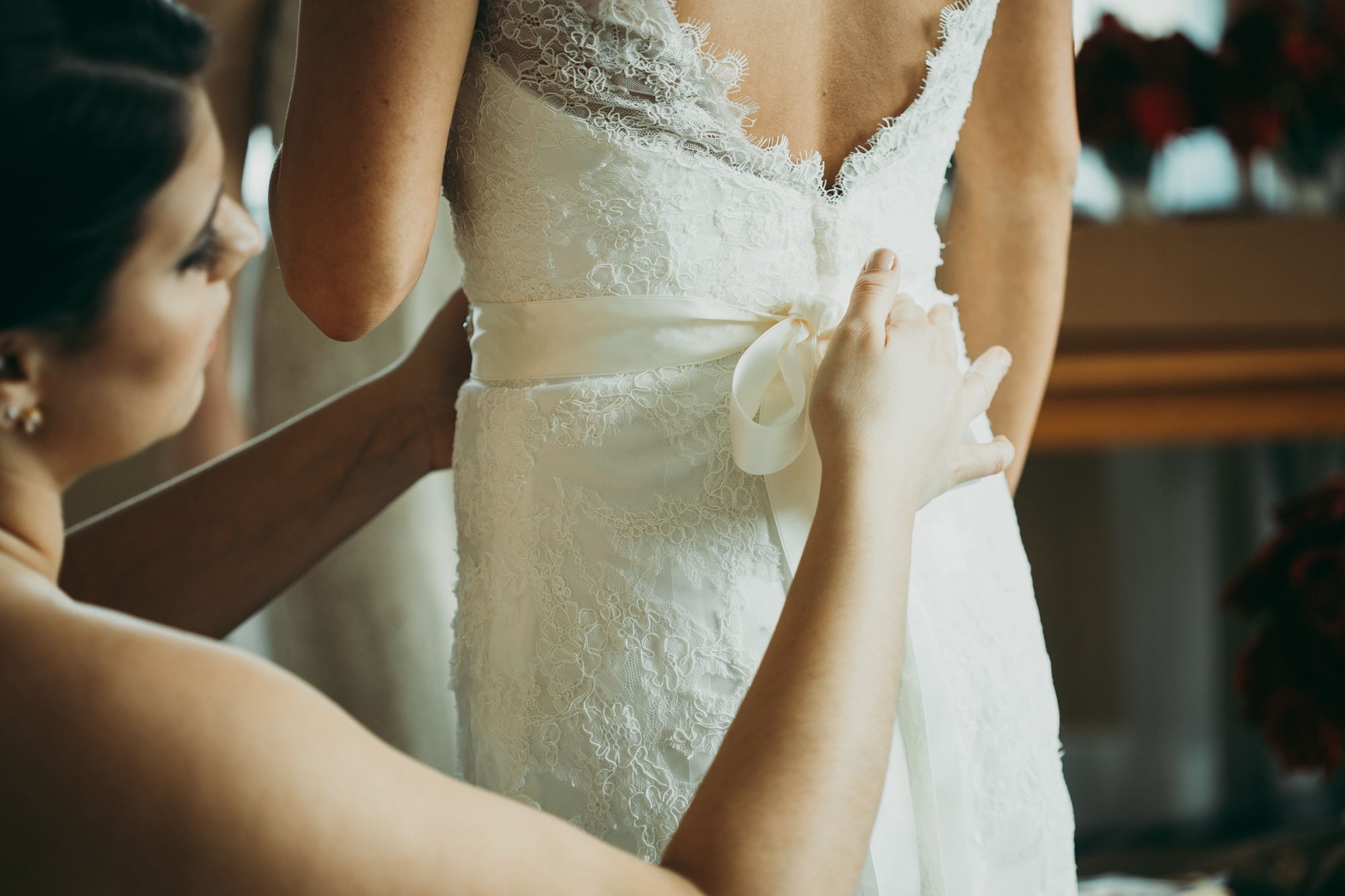 Bridesmaid helping bride put on her lace wedding gown.