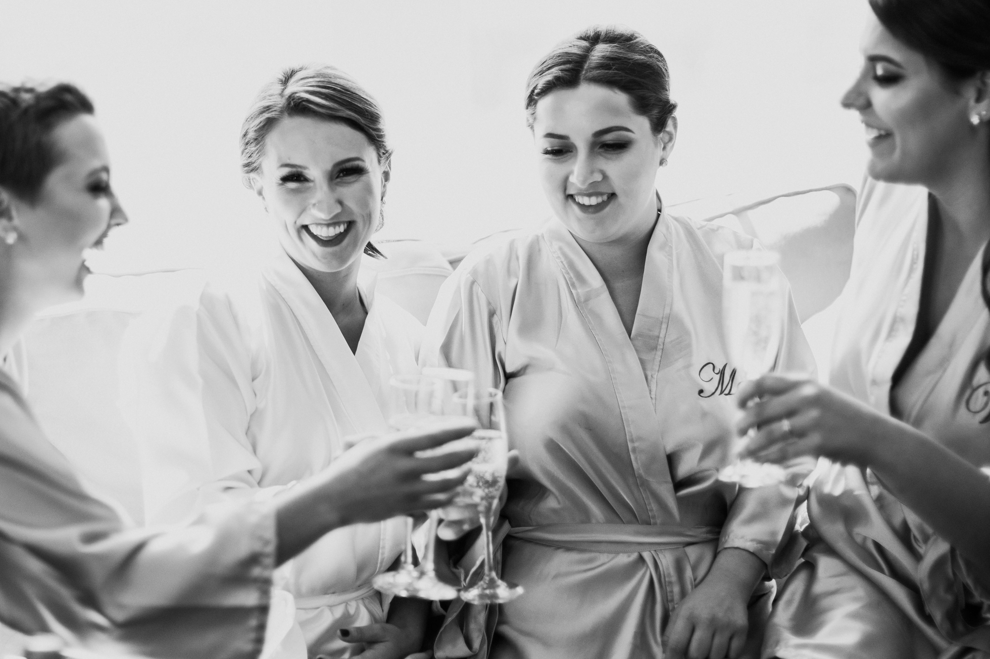 Three bridesmaid and a bride sitting together enjoying champagne and laughing while wearing bridal robes.