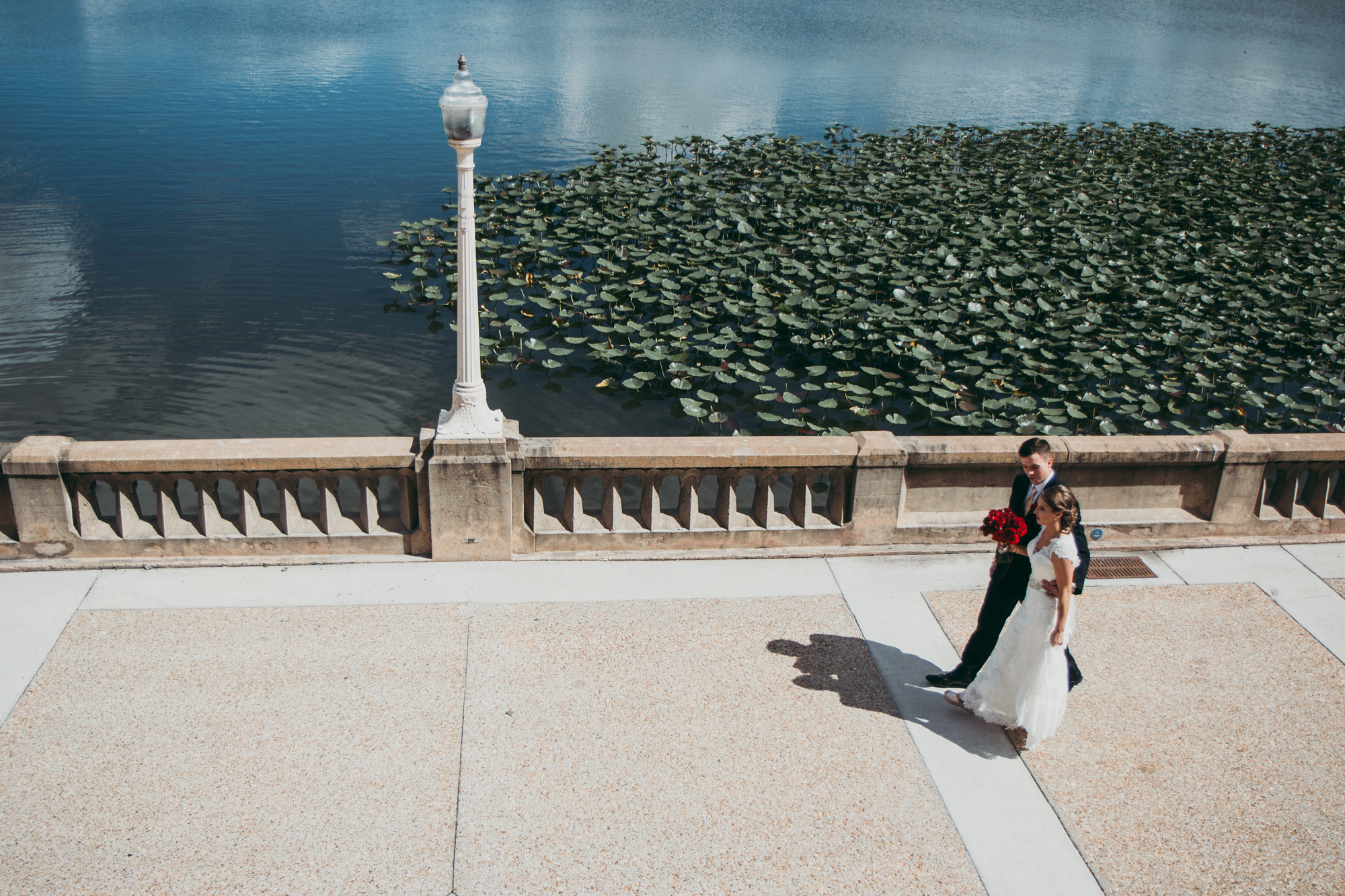 Bride and groom walking together next to a lake on a sunny day.