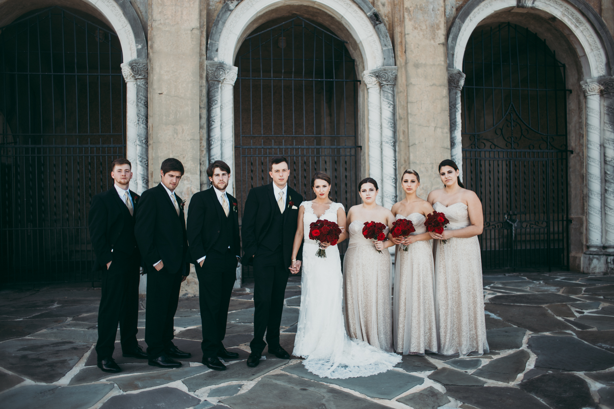 Bridal party standing together in a line looking at the camera. Bridesmaid are holding red rose bouquets.