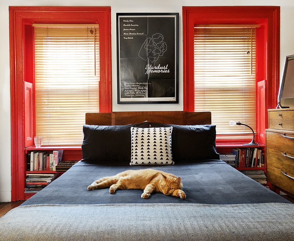 1930's Art Deco bed frame, custom red shelves, vintage film poster and original lamp by local artisan.