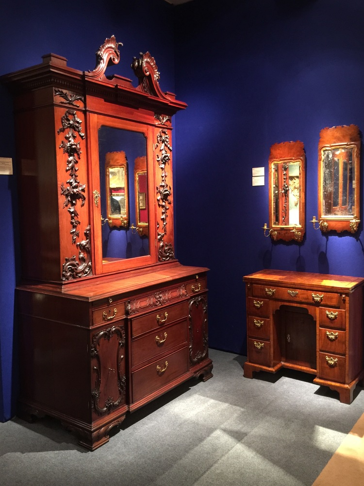 Wooden case pieces in a vignette from Hyde Park Antiques are made even more special with the cobalt blue walls.