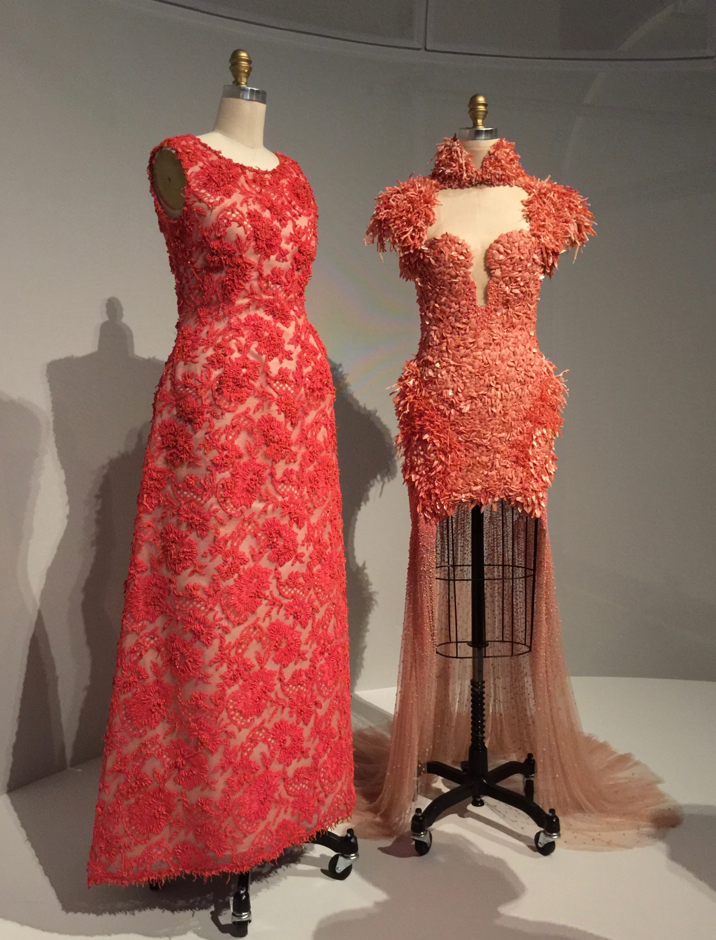 (l) HOUSE OF GIVENCHY, Hubert de Givenchy DRESS, 1963, haute couture  Hand-sewn red-orange cotton Mechlin-type lace hand-embroidered with red-orange glass beads, tinsel, and pieces of coral  (r) ALEXANDER MCQUEEN, Sarah Burton DRESS, Spring/Summer 2012,pret-a-porter