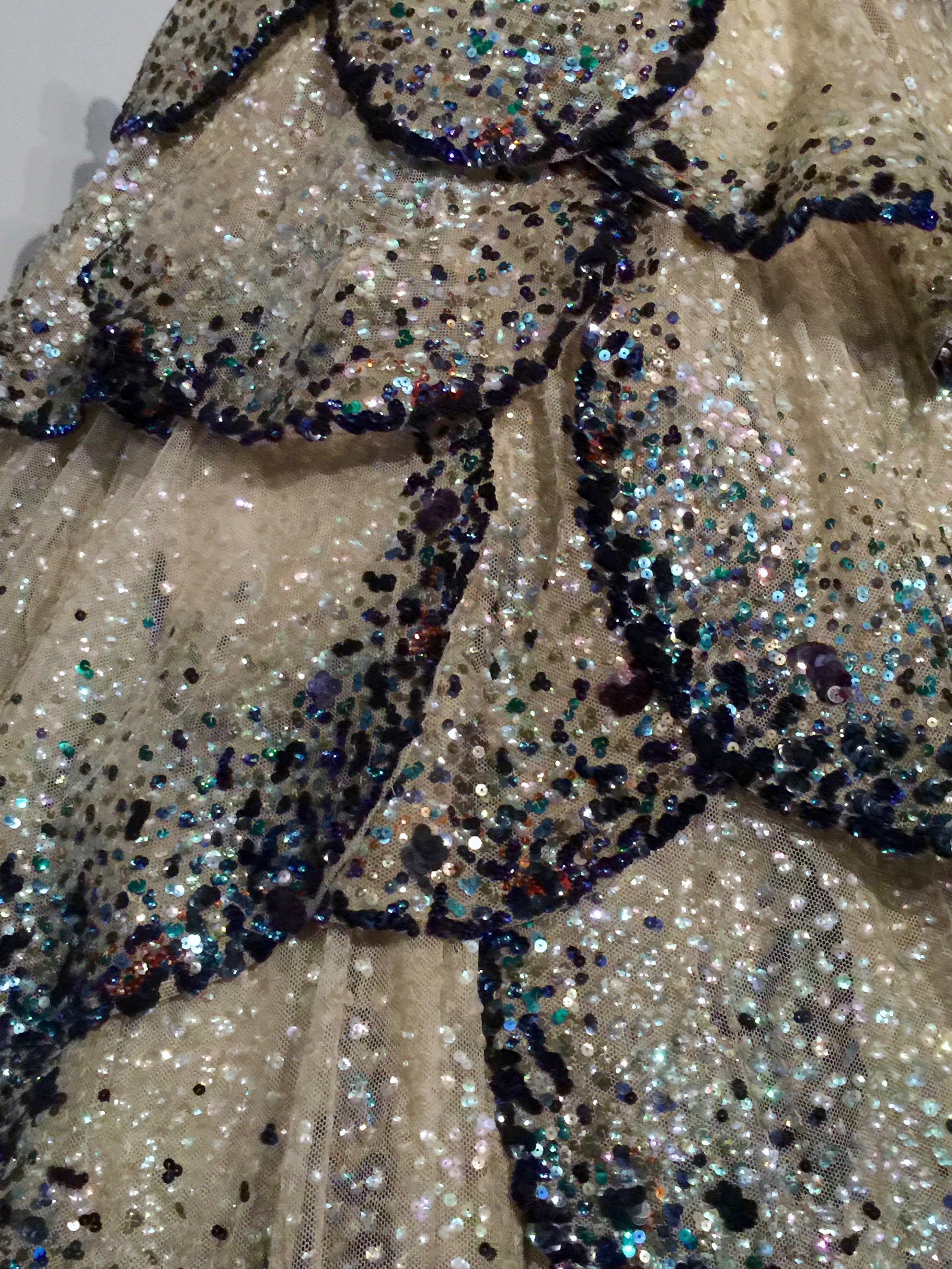Detail of the hand-embroidered opalescent, blue, green, and orange gelatin sequins.