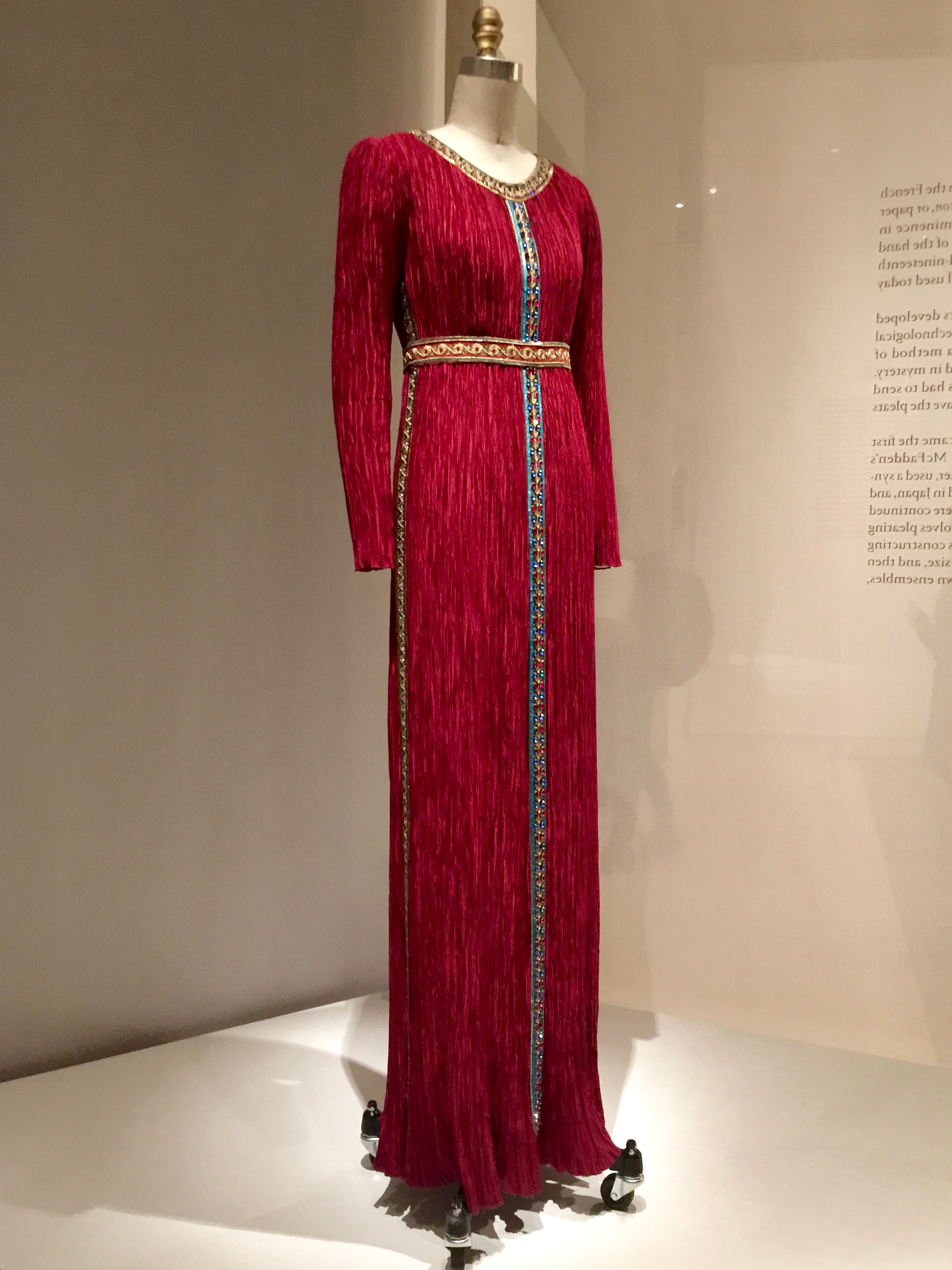 """Mary McFadden  DRESS, Ca. 1980,pret-a-porter  Machine-sewn and """"Marii"""" machine-pleated red polyester charmeuse, hand-stitched with hand-embroidered trims of sequins, bead, and gold metallic thread"""
