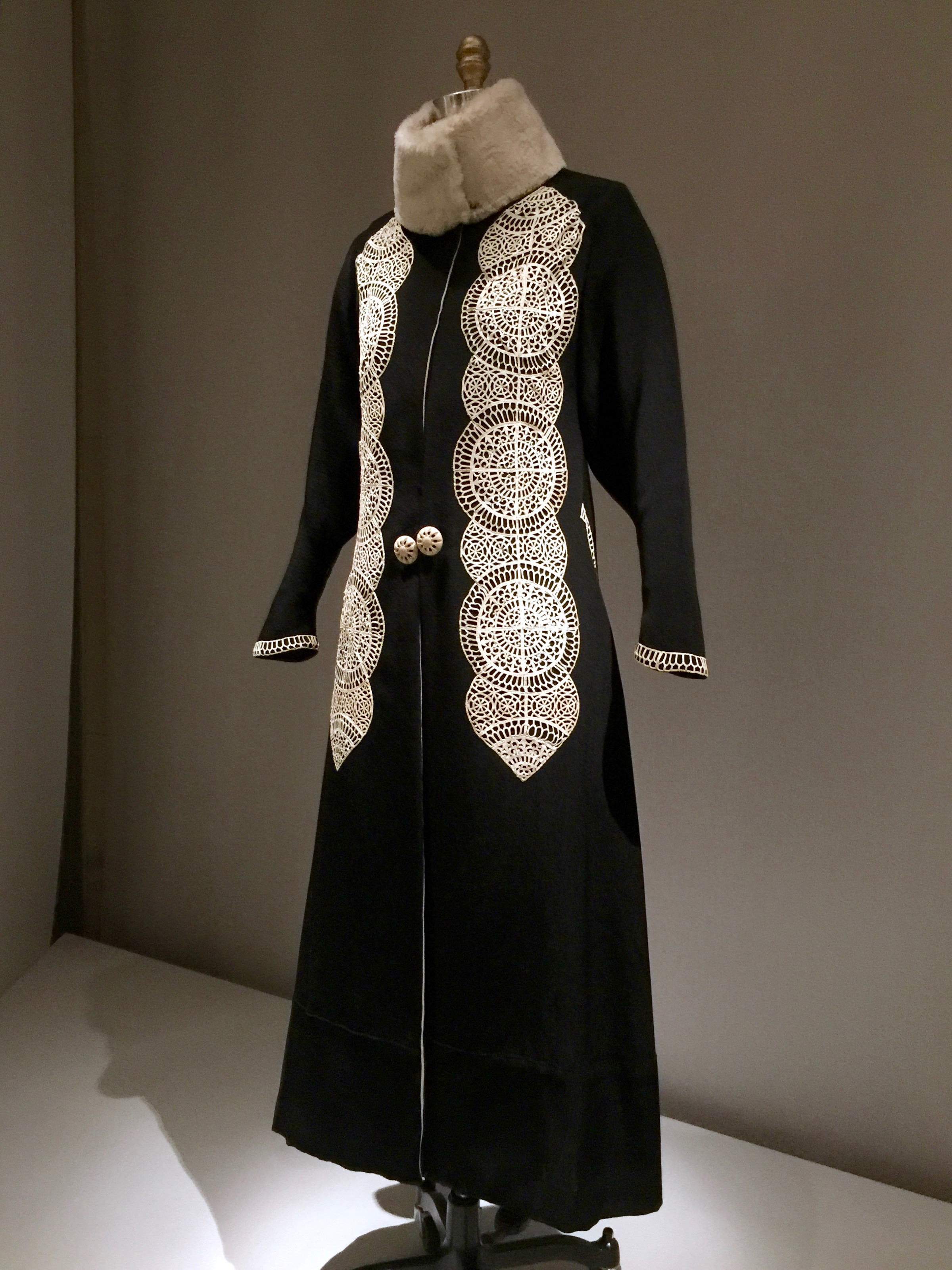 Paul Poiret COAT, Ca. 1919, haute couture  Machine-sewn black wool rep with white fur collar, hand-appliquéd with white kidskin cutwork, hand-sewn hem and silk binding