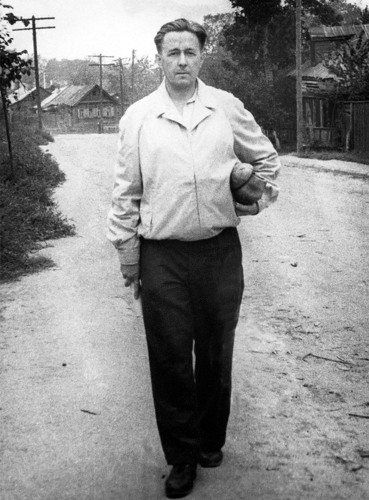 5.3 ┆   Walking home in Ryazan, along Kasimovskiy  Street, from a bakery.    In author's left hand are loaves of black and white bread, in his right—a newspaper.